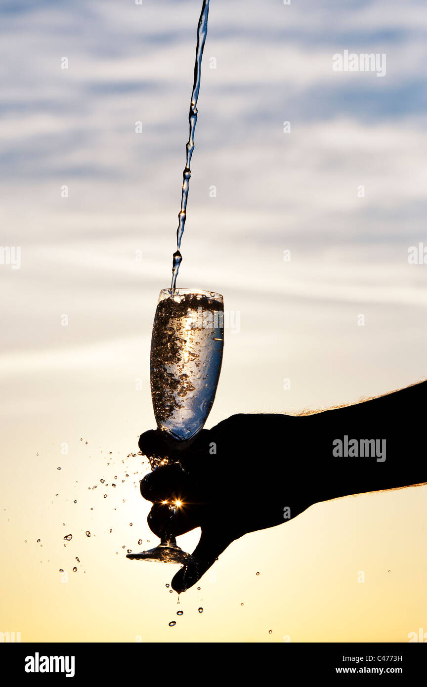 Water being poured into a champagne flute. Silhouette - Stock Image