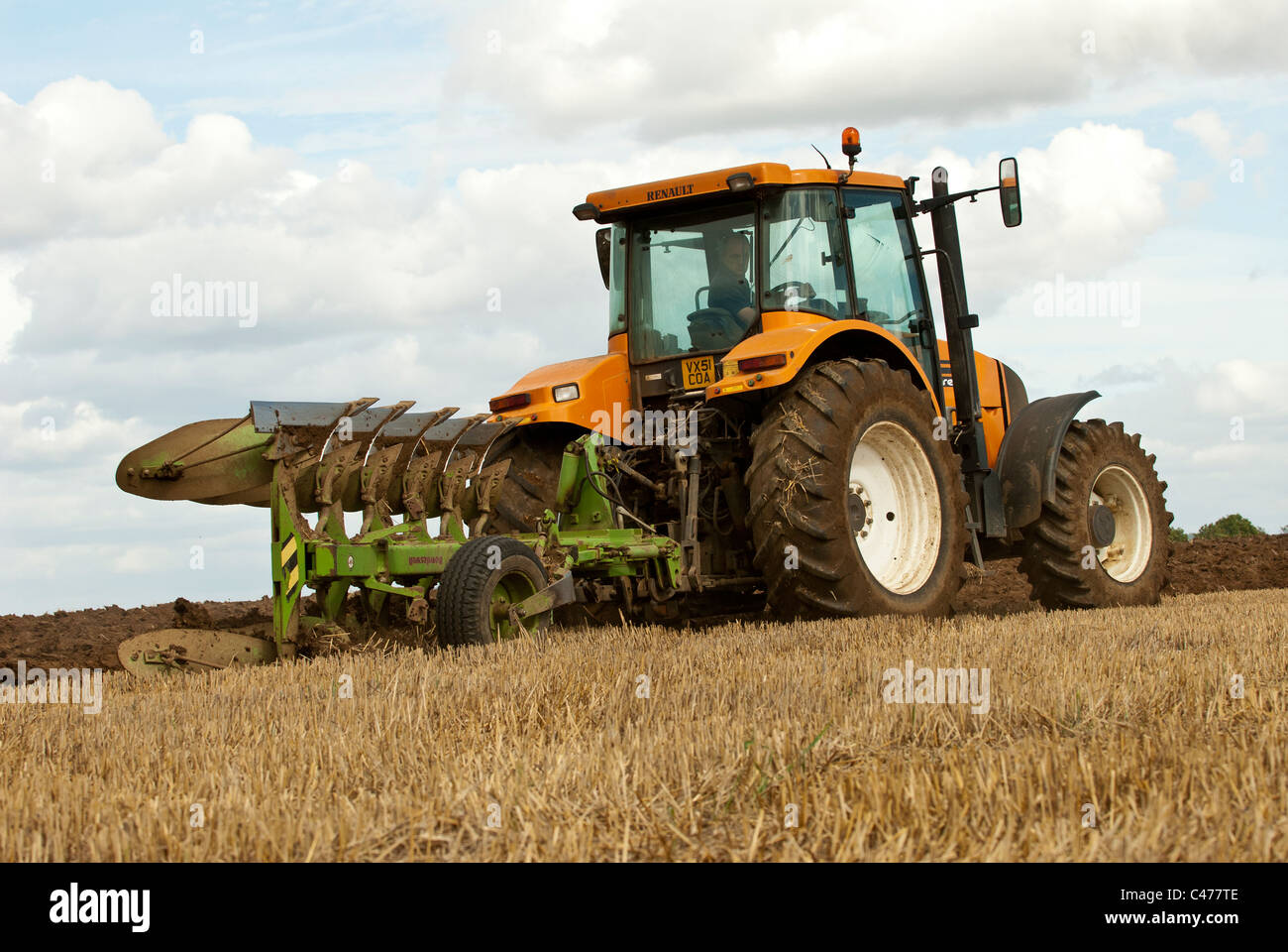 Renault Tractor ploughing a field after harvesting is completed - Stock Image