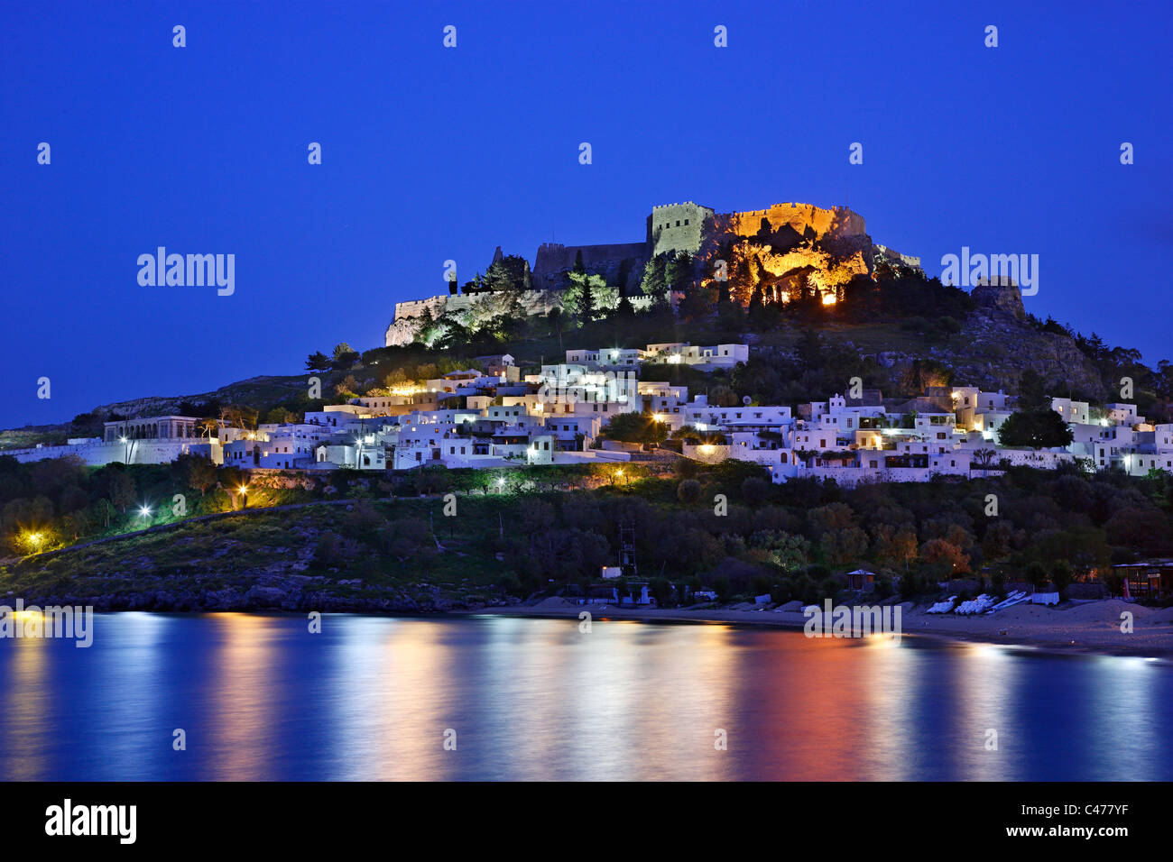Beautiful Lindos village with its castle (Acropolis) in the 'blue' hour. Rhodes island, Dodecanese, Greece - Stock Image