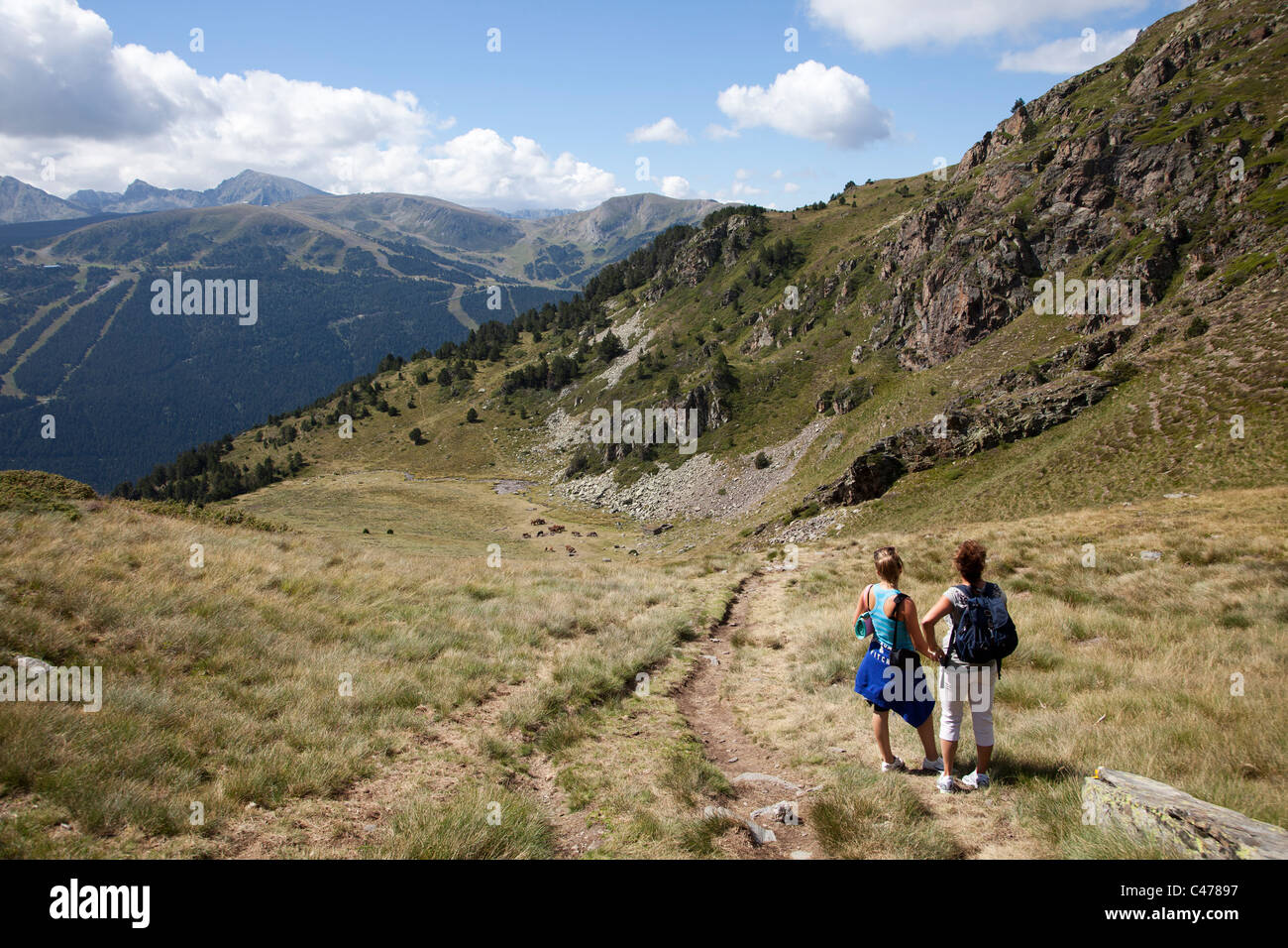 Two people admiring view in mountains on the Asses de les Salamandres walk Vall d'Incles Andorra - Stock Image