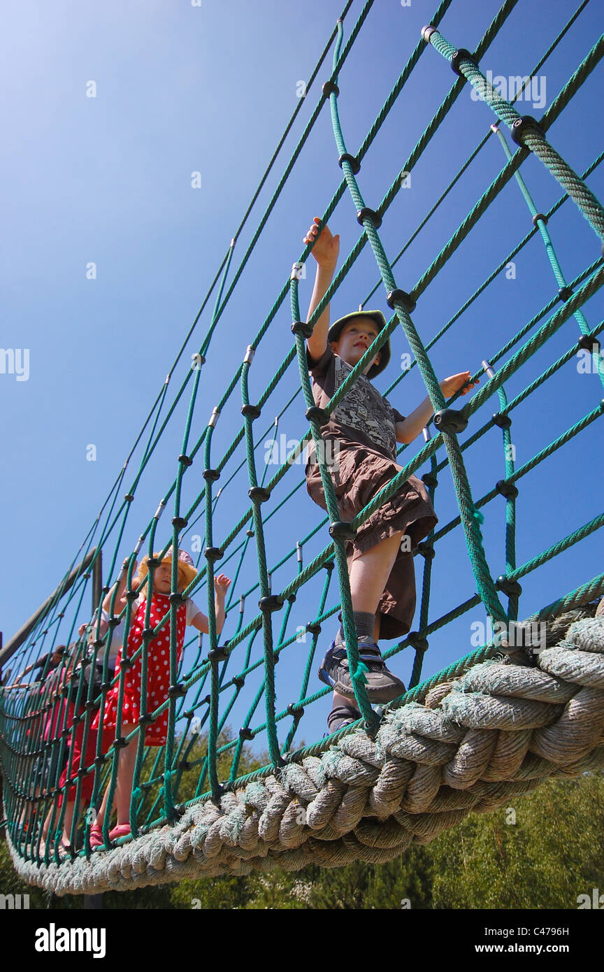 Children walking across a rope bridge. View from below. - Stock Image