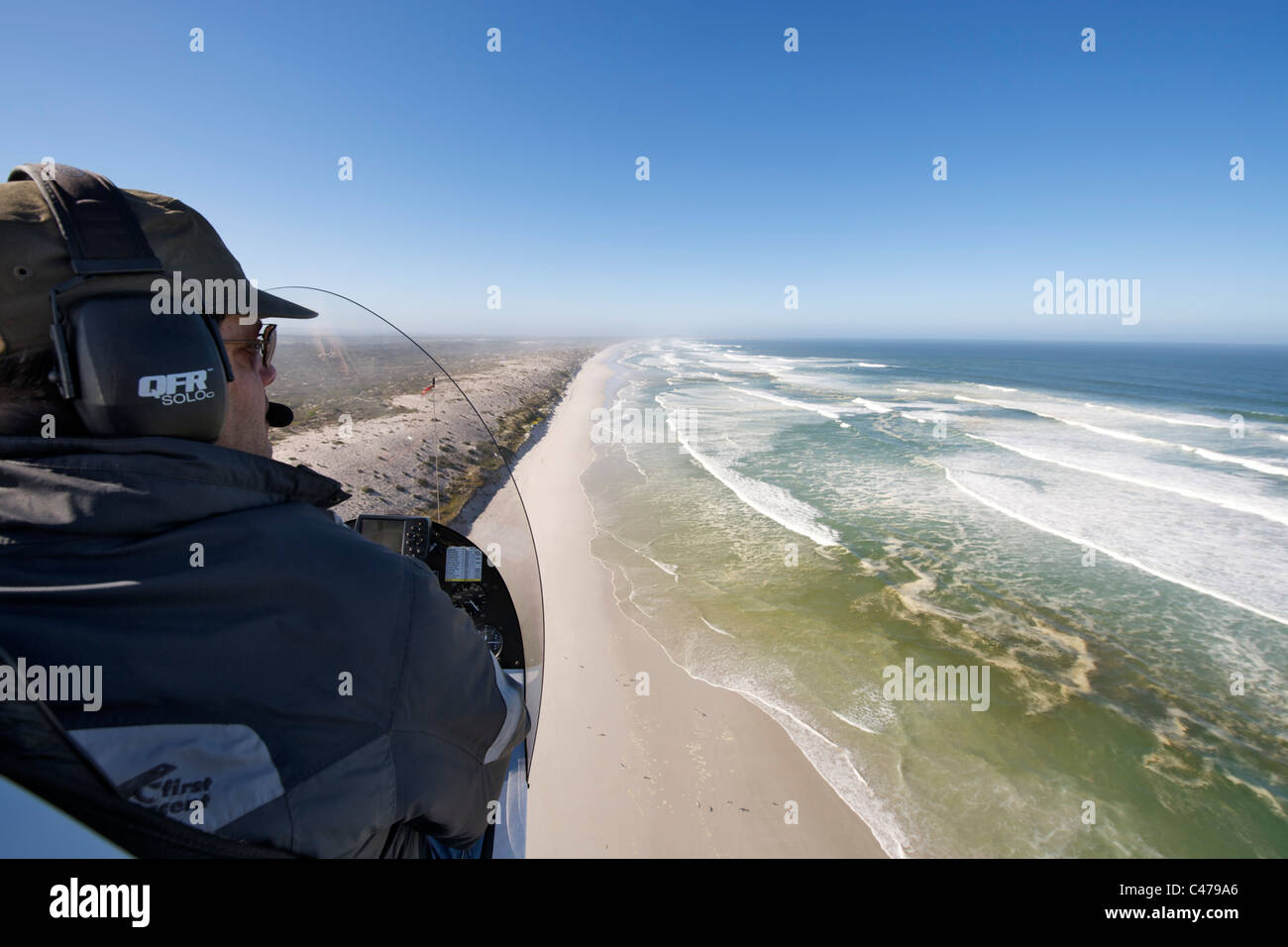 Aerial view over the shoulder of a gryocopter pilot flying along the beach near Yzerfontein north of Cape Town in Stock Photo