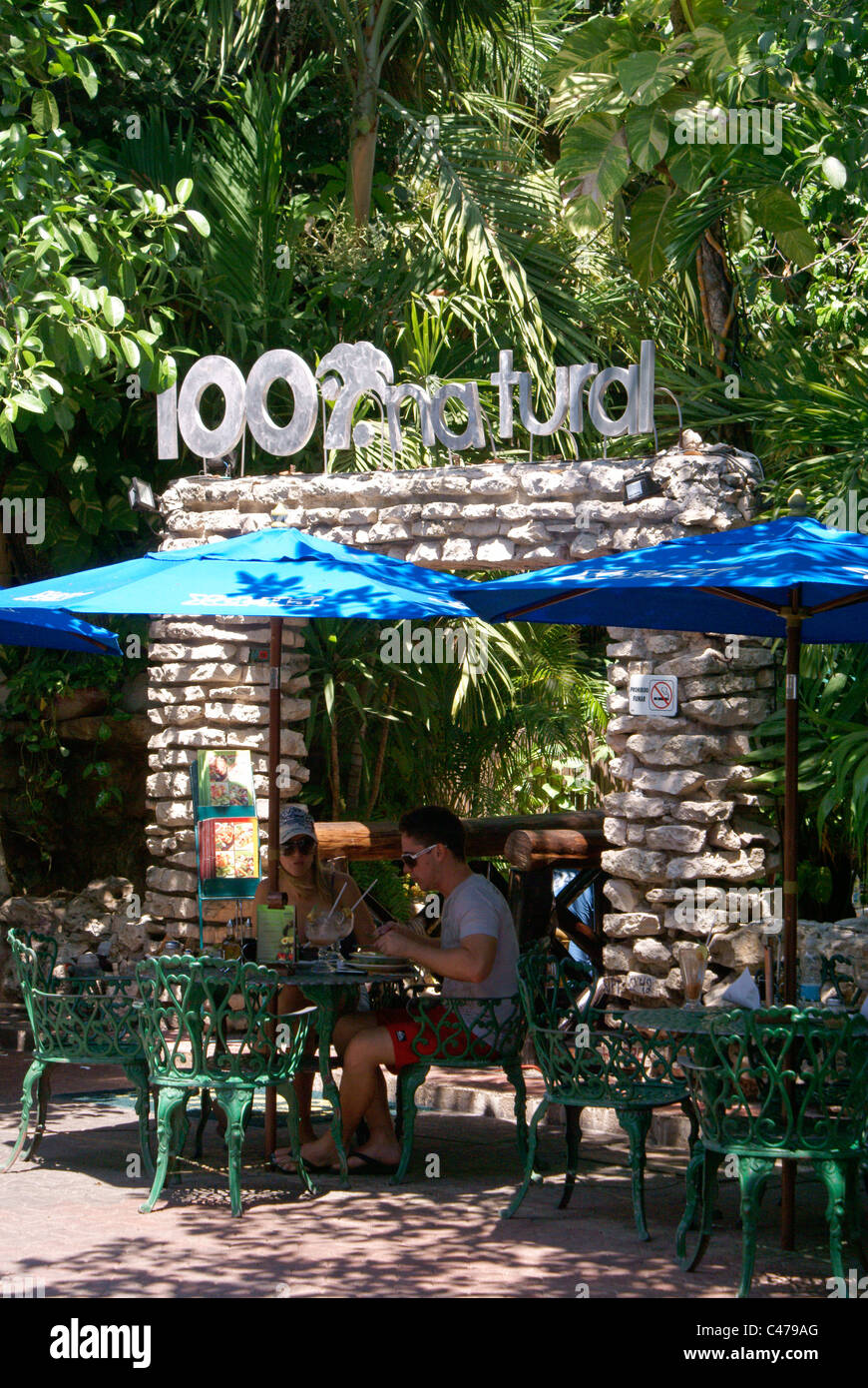 Tourist couple in one One Hundred Percent Natural restaurant on Fifth Avenue or Quinta Avenida, Playa del Carmen, - Stock Image