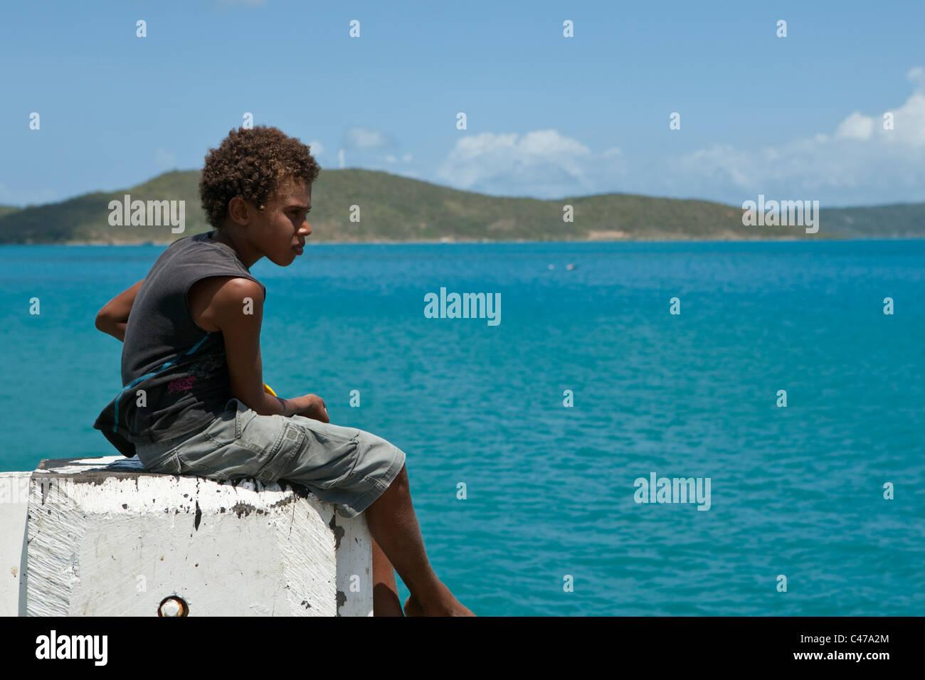 Torres Strait Islander boy fishing off the jetty at Horn Island, Torres Strait Islands, Queensland, Australia - Stock Image