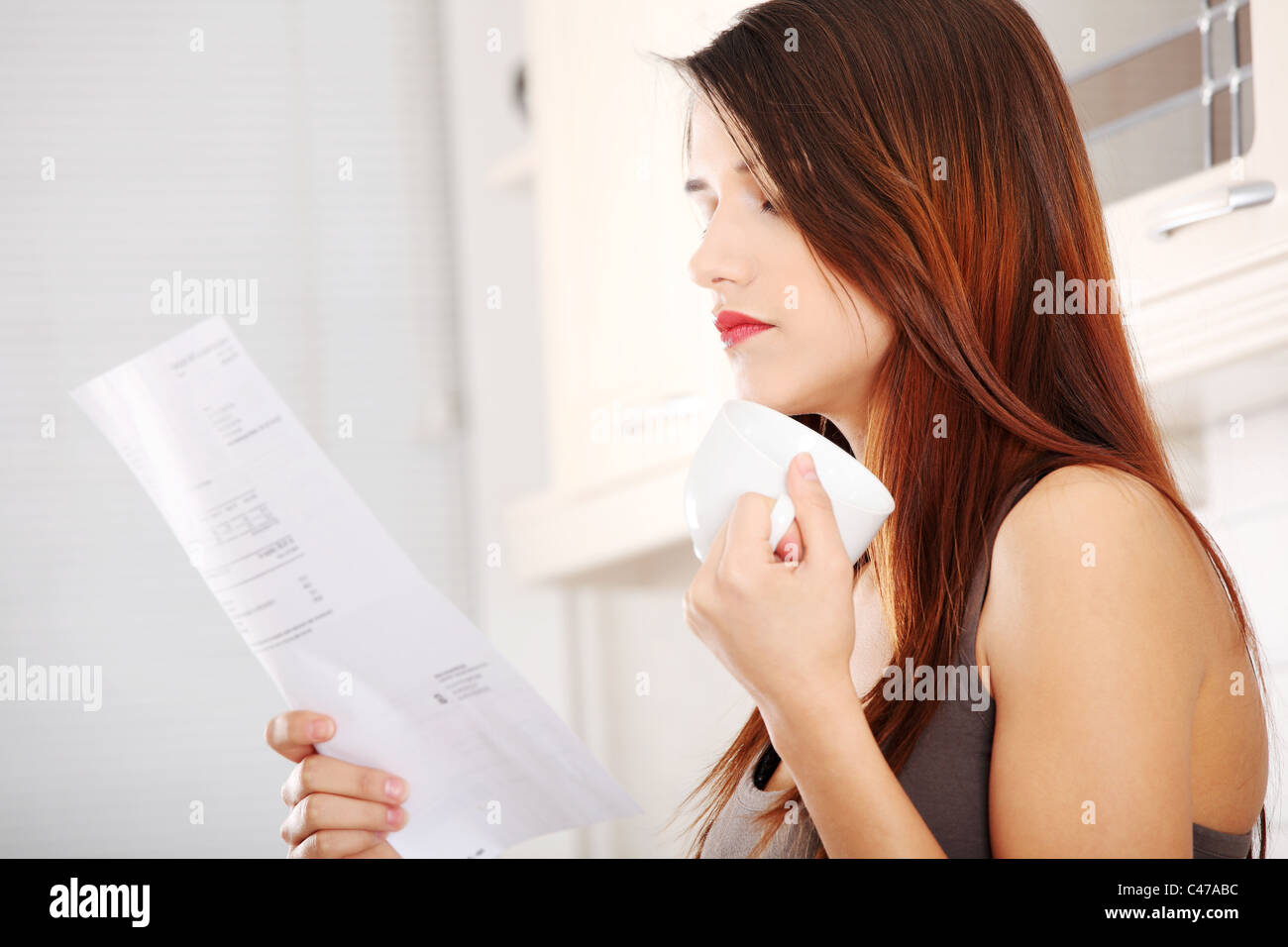 Stressed young caucasian woman in the kitchen drinking something hot ...