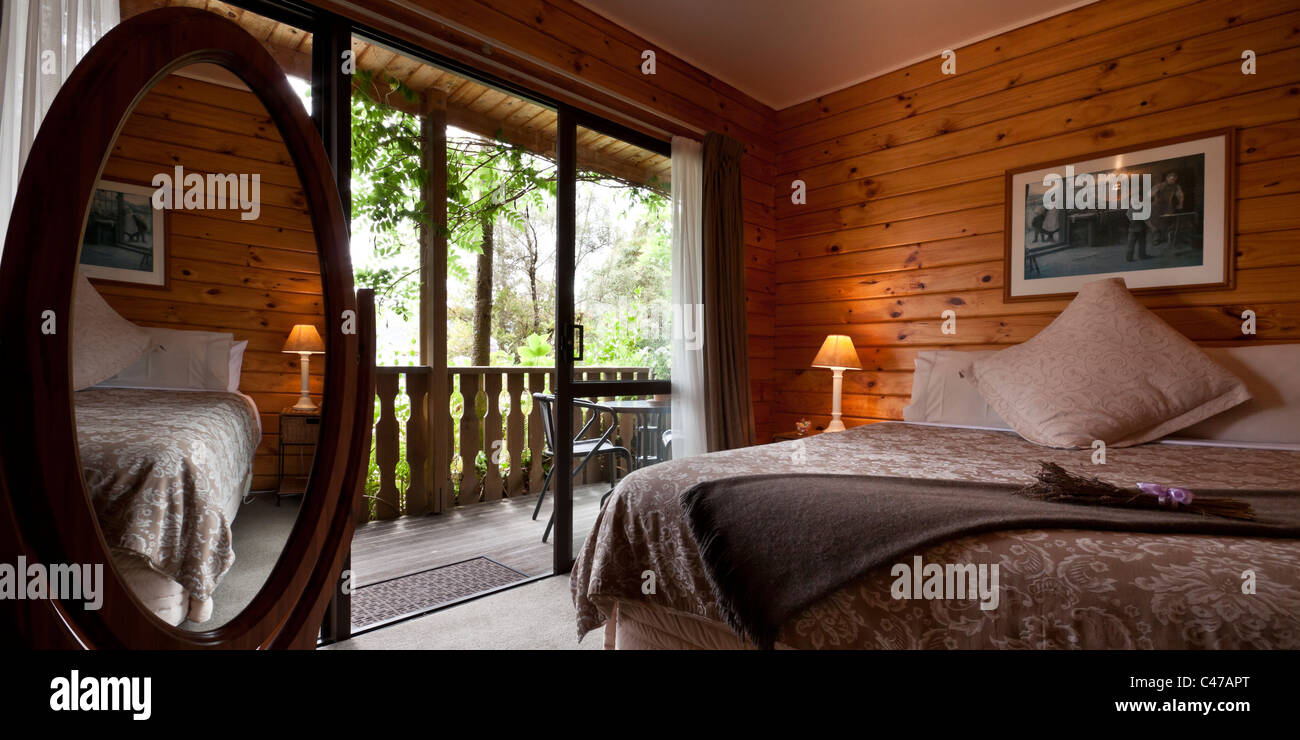 Nice warm bedroom interior of mountain lodge. Fox Glacier Lodge, Fox Glacier, West Coast, South Island, New Zealand. - Stock Image