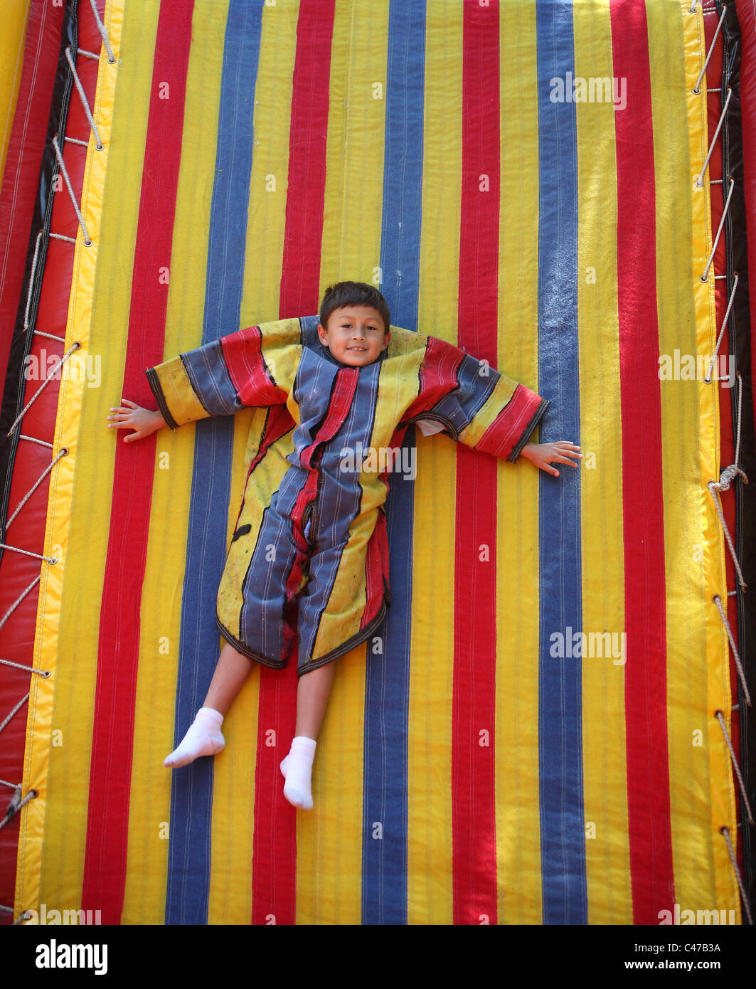 Boy playing on velcro sticky wall in colorful suit - Stock Image