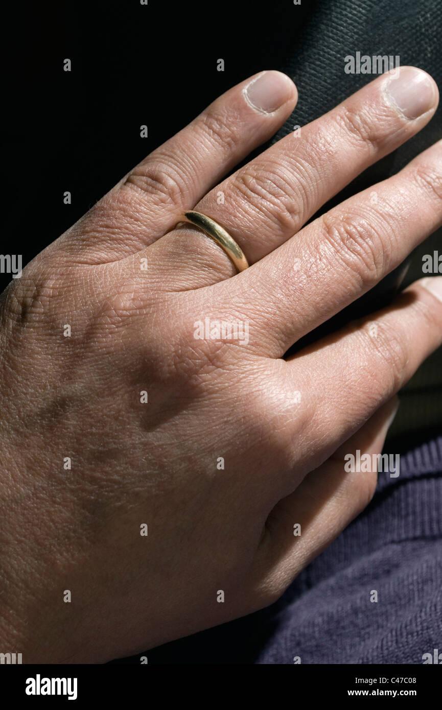 wedding ring on man's hand - Stock Image
