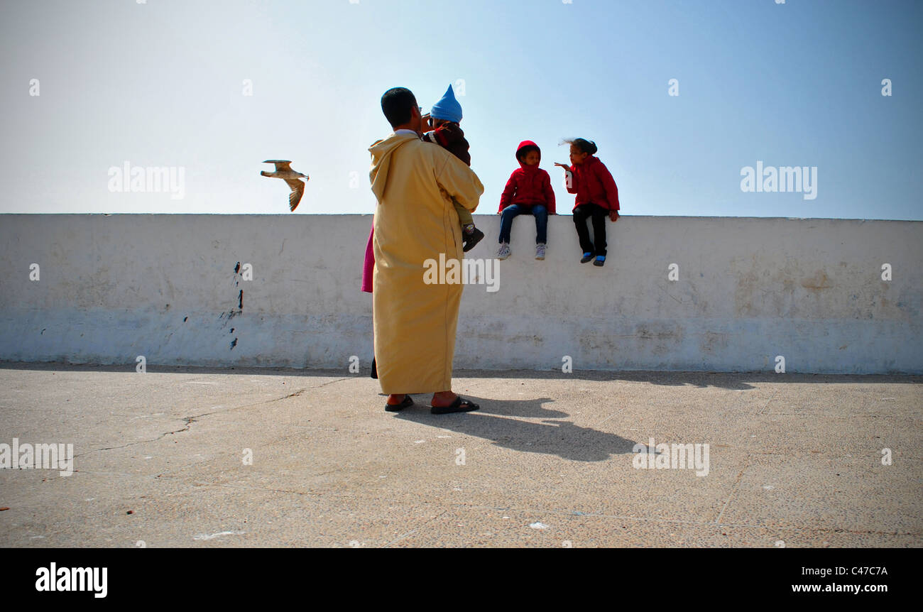 Moroccan family by the sea wall in Essaouira, Morocco Stock Photo