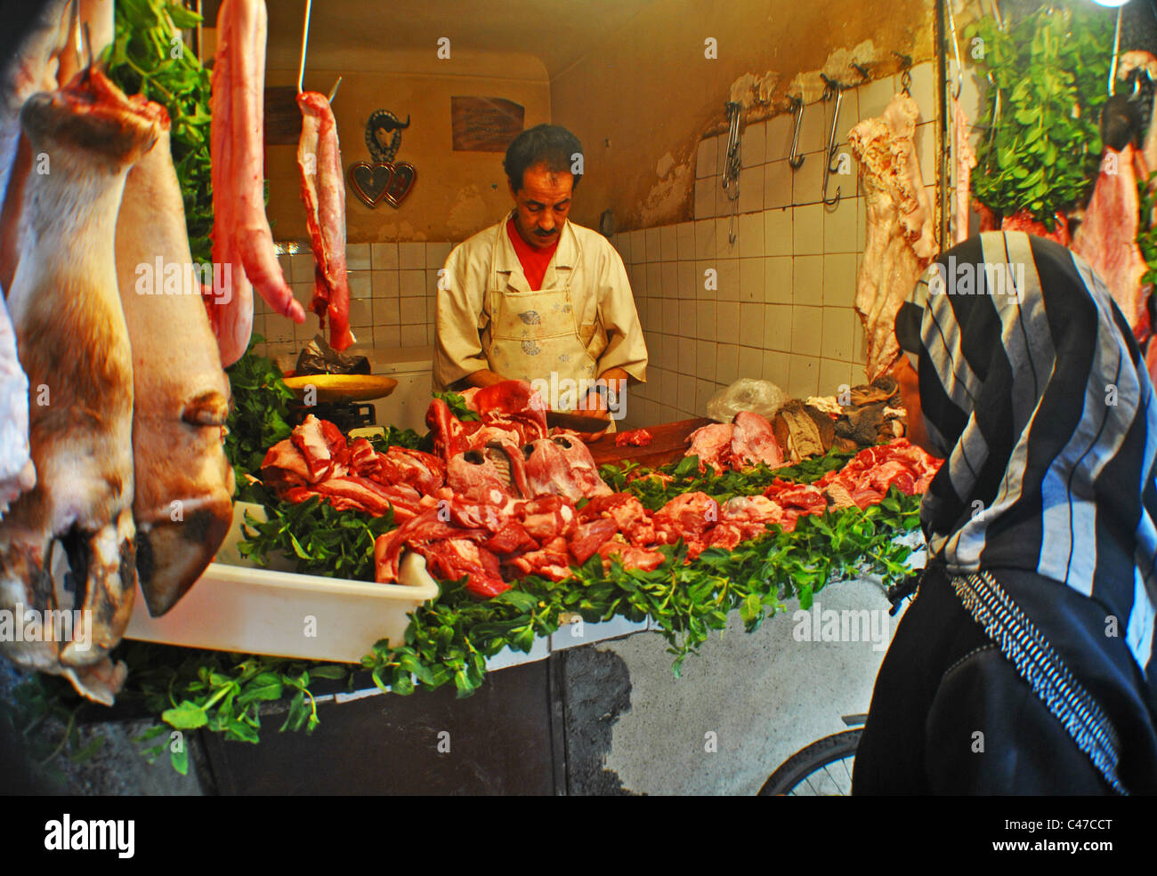 Woman buying from a butcher's in Marrakesh, Morocco Stock Photo