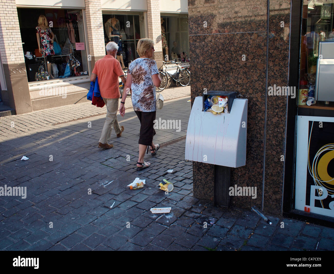 Dirty street with overflowing garbage bin, Breda, Noord Brabant, the Netherlands - Stock Image