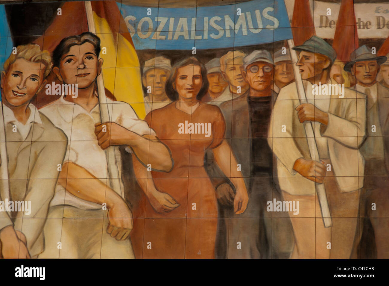 Socialist realist mural on a building in Berlin, Germany depicting young male and female musicians leading a parade. - Stock Image