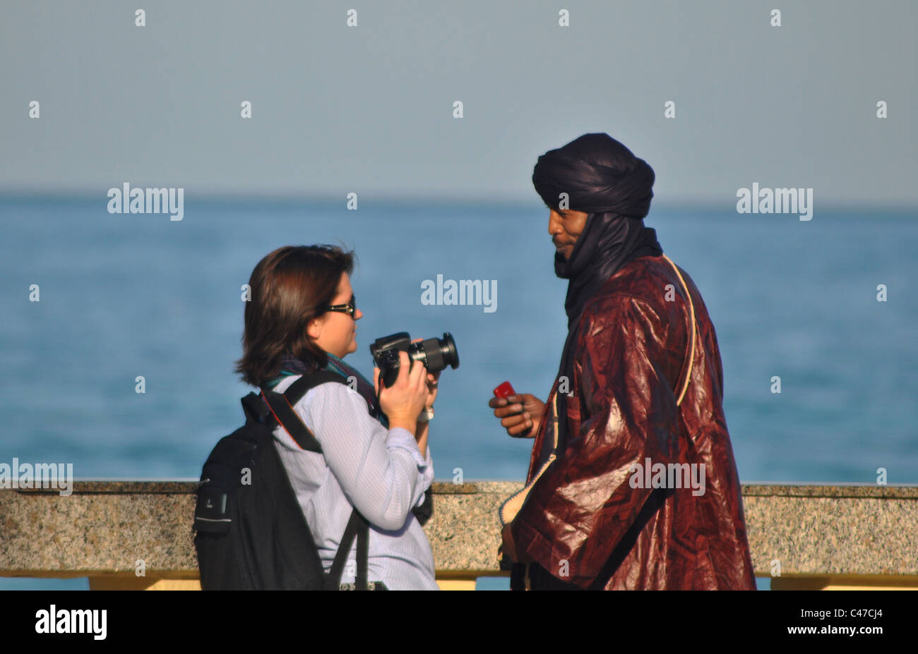 Woman taking a photo of a Tunisian man in Sousse, Tunisia - Stock Image