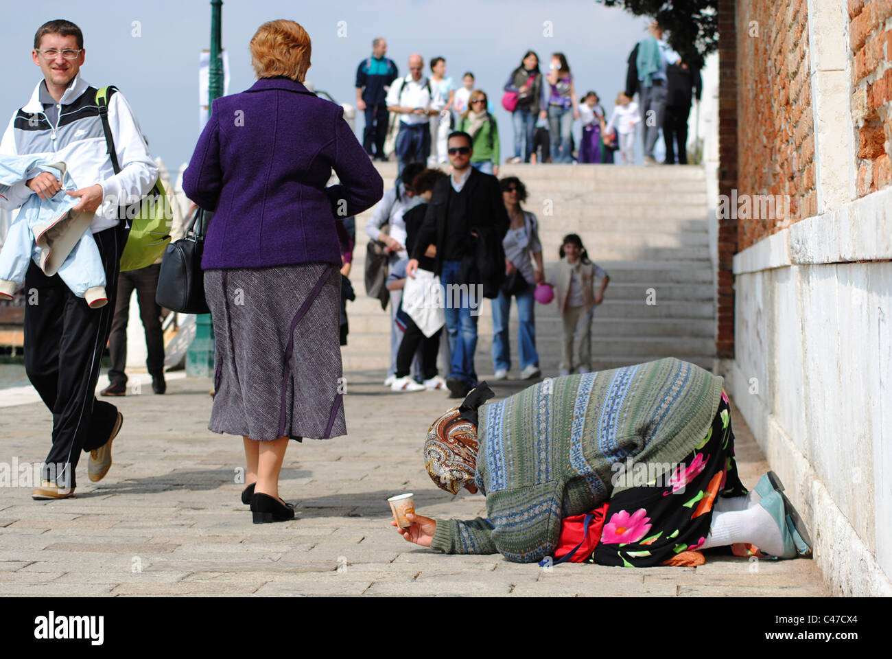 Woman begging in Venice, Italy - Stock Image