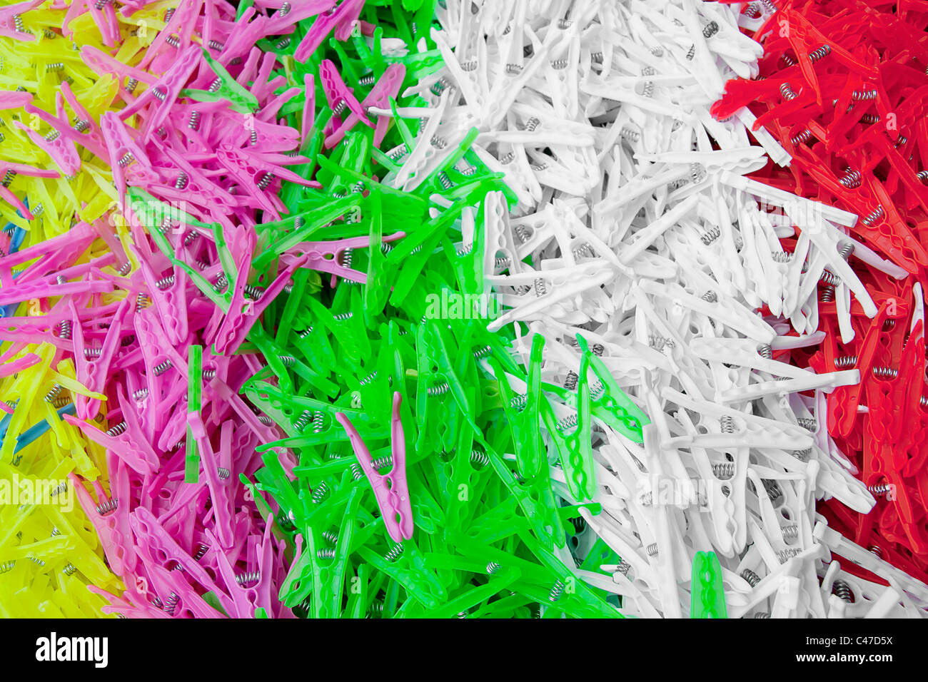 Different colored plastic clothes pins on a counter in an open marketplace Stock Photo