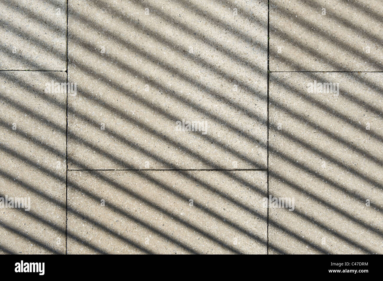 A metal fence casts a long shadow onto a flagstone pavement on a bright and sunny day. - Stock Image