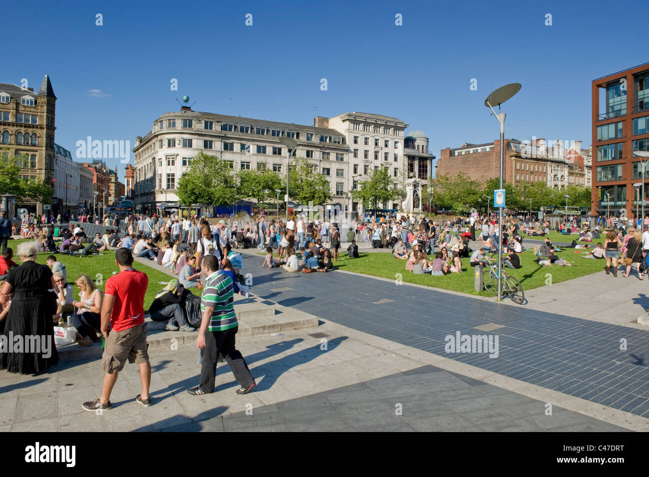 People congregate in the crowded Piccadilly Gardens, Manchester on a hot, sunny day. - Stock Image