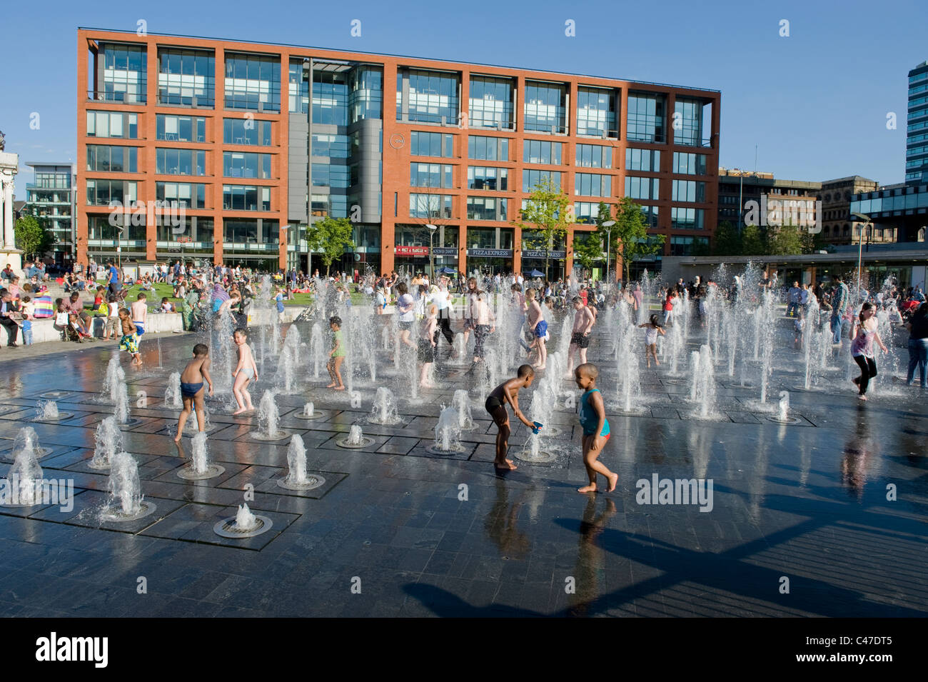 Children play in a fountain in Piccadilly Gardens, Manchester on a hot, sunny day. - Stock Image