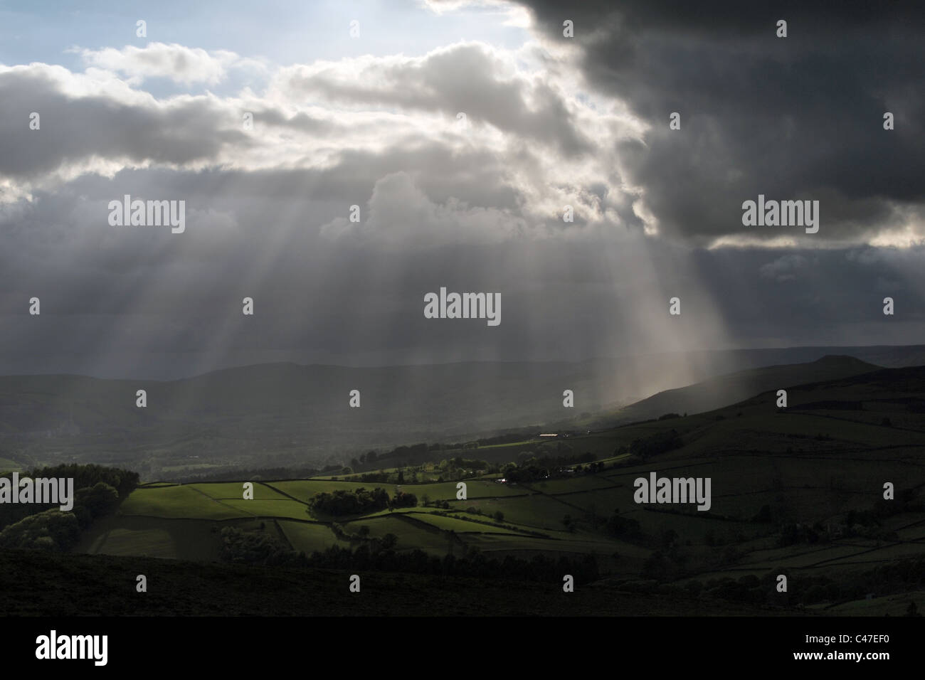 beautiful sunburst sun rays bursting through clouds shines light over the countryside in the Peak District Derbyshire - Stock Image