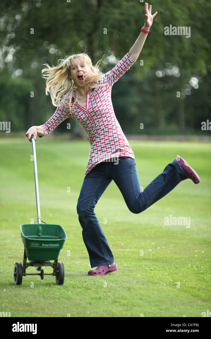 Woman playing to the camera with seed spreader - Stock Image