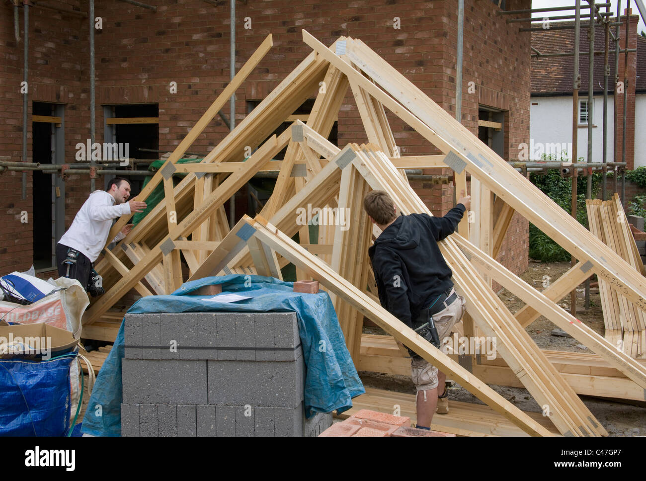 Two workers checking a delivery of roof trusses. - Stock Image