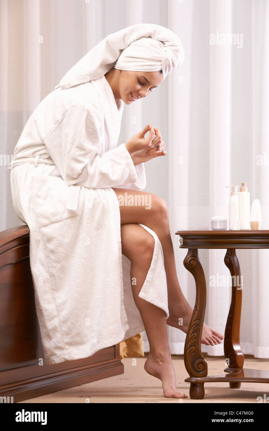 Portrait of pretty female taking care of herself after bath - Stock Image