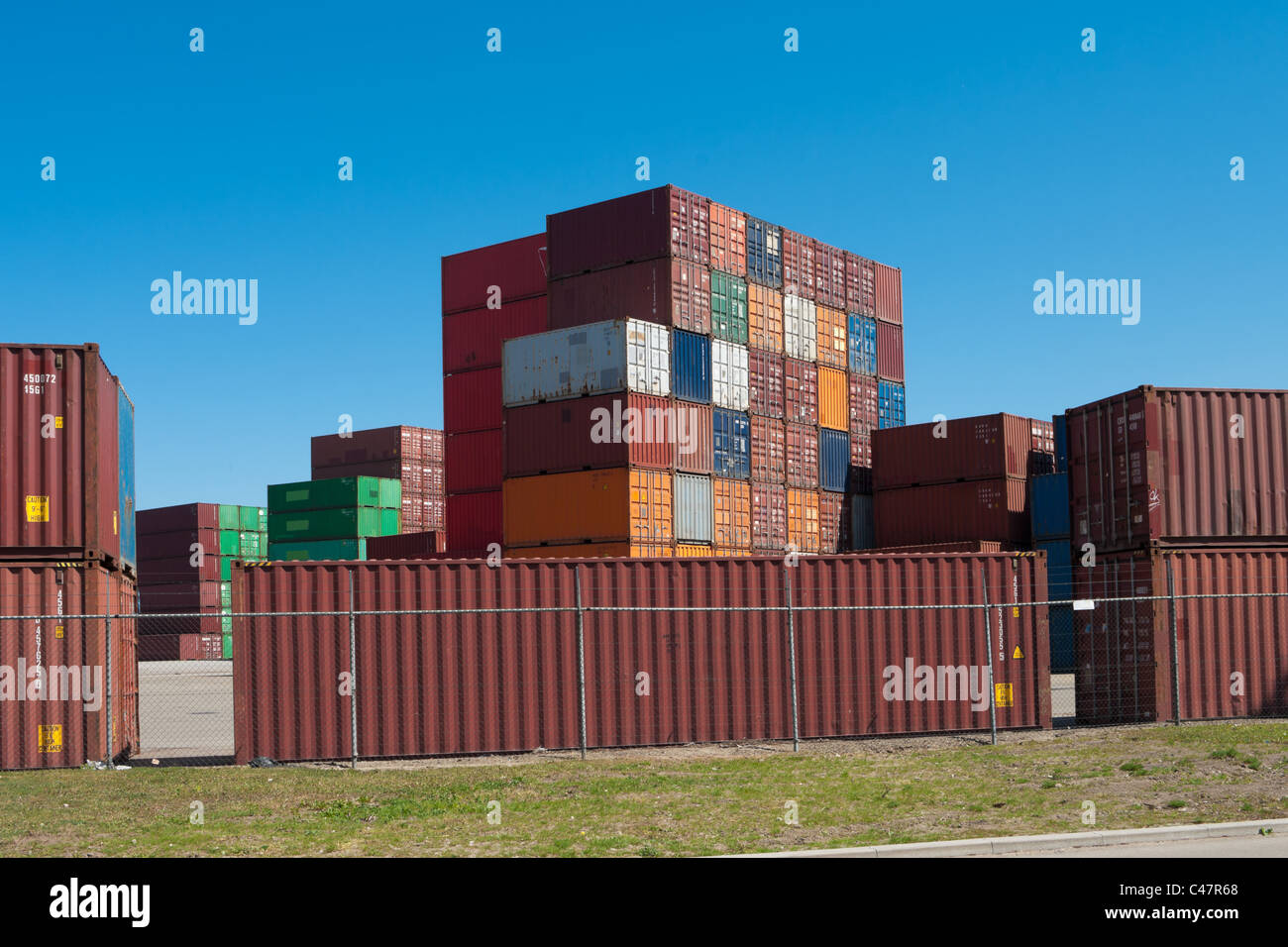 sea containers piled up on a large industrial area in the port of Rotterdam - Stock Image