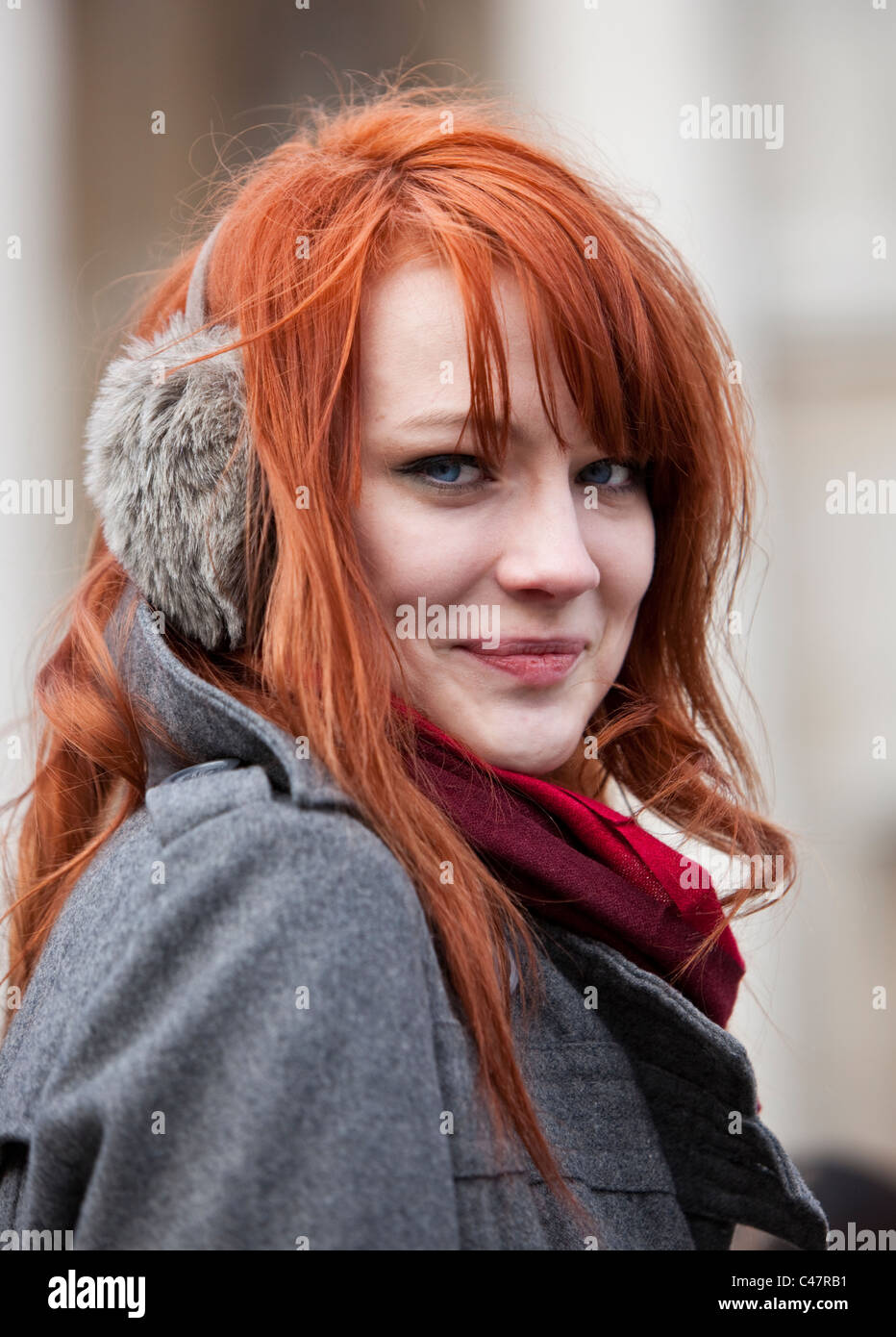 Headshot portrait of a ginger haired teenager wearing earmuffs in winter, London, England, UK, GB. Stock Photo