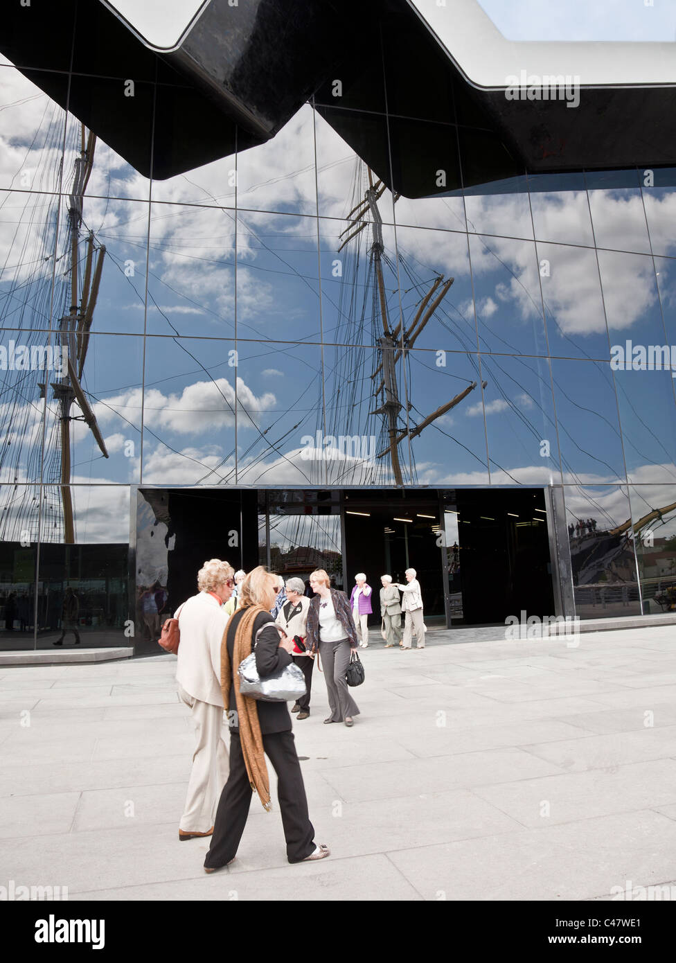 Visitors outside the Riverside Museum, Glasgow. The masts of the Glenlee (Tall Ship) are reflected in the glass - Stock Image