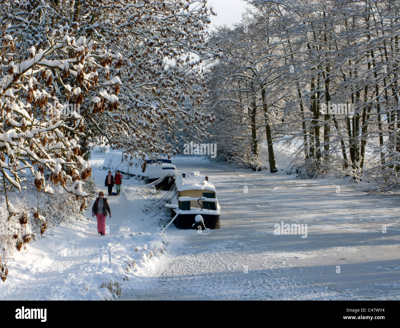 Walkers on the towpath of a frozen Birmingham and Worcester Canal at Alvechurch, Worcestershire, England - Stock Image