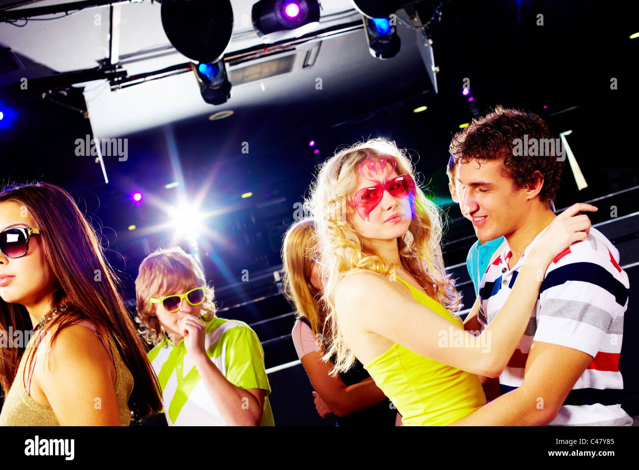 Portrait of happy glamorous friends during party in a night club - Stock Image