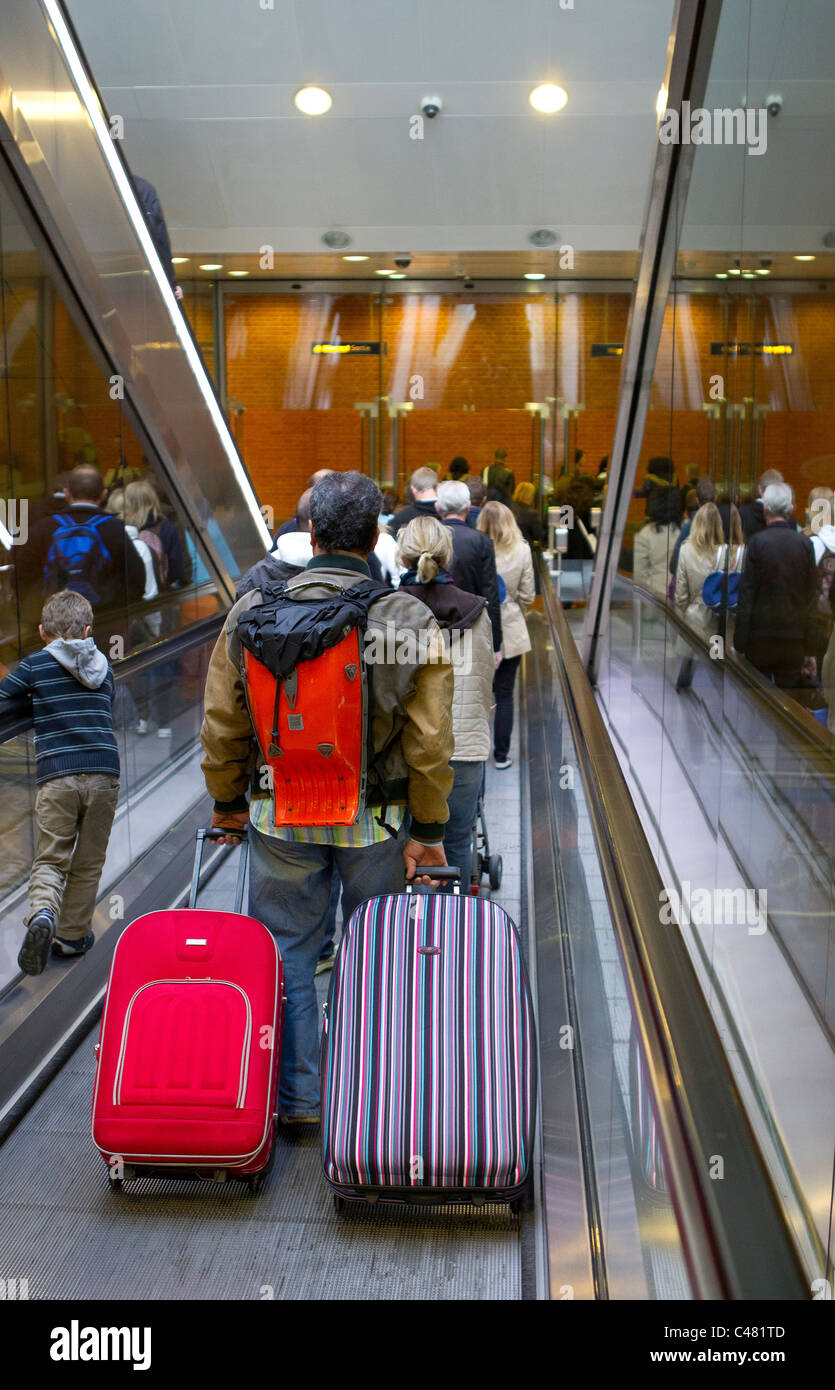 man with luggage on escalator - Stock Image
