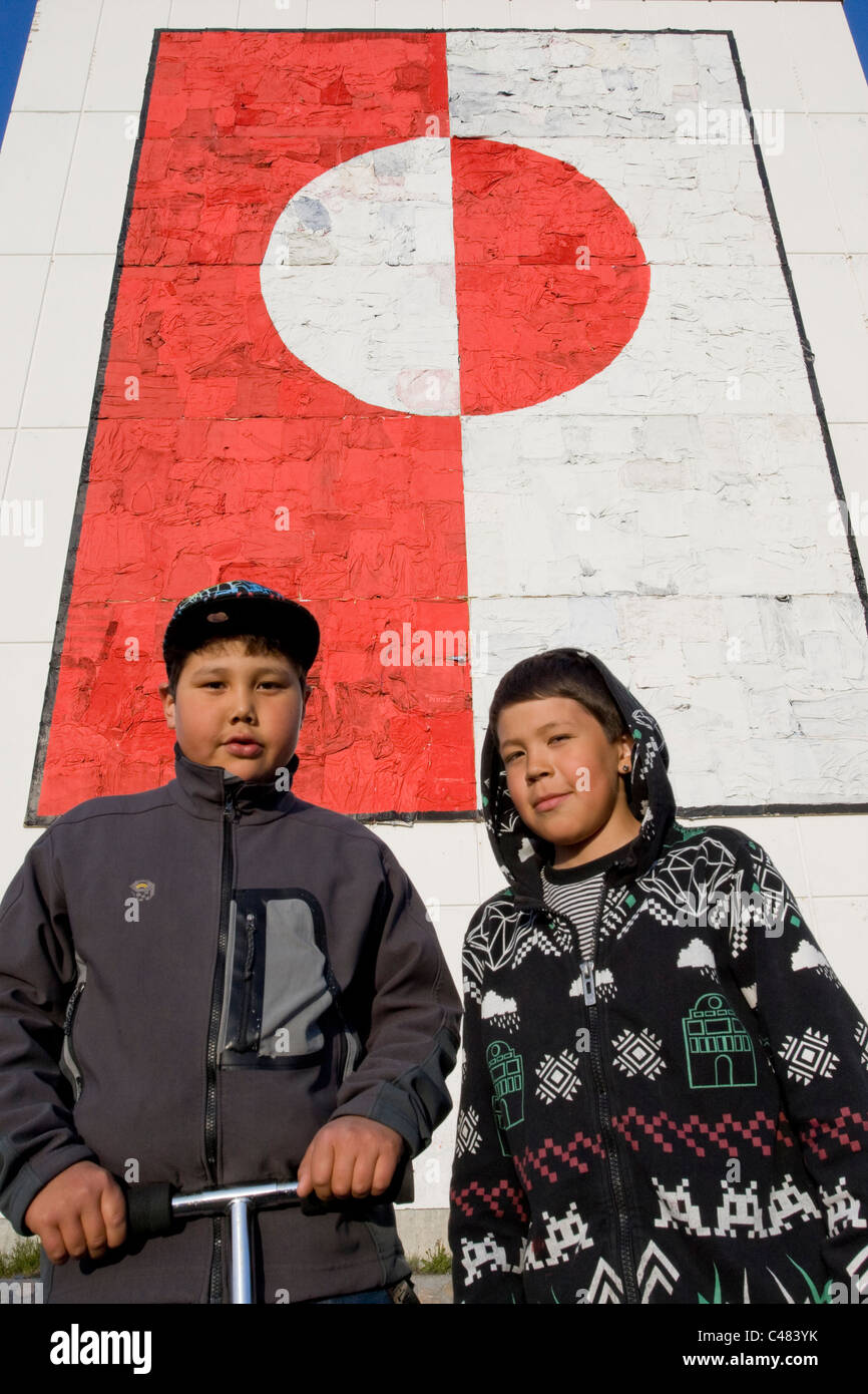 Two local boys in front of a large painting of the Greenland flag in Nuuk, Greenland - Stock Image