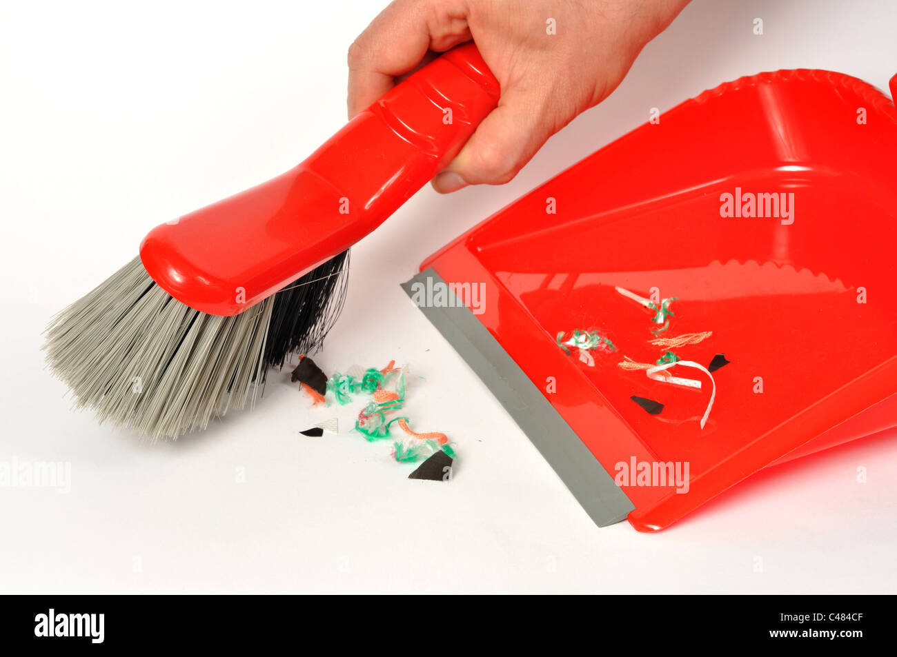 Red brush and dustpan with some garbage on white background - Stock Image