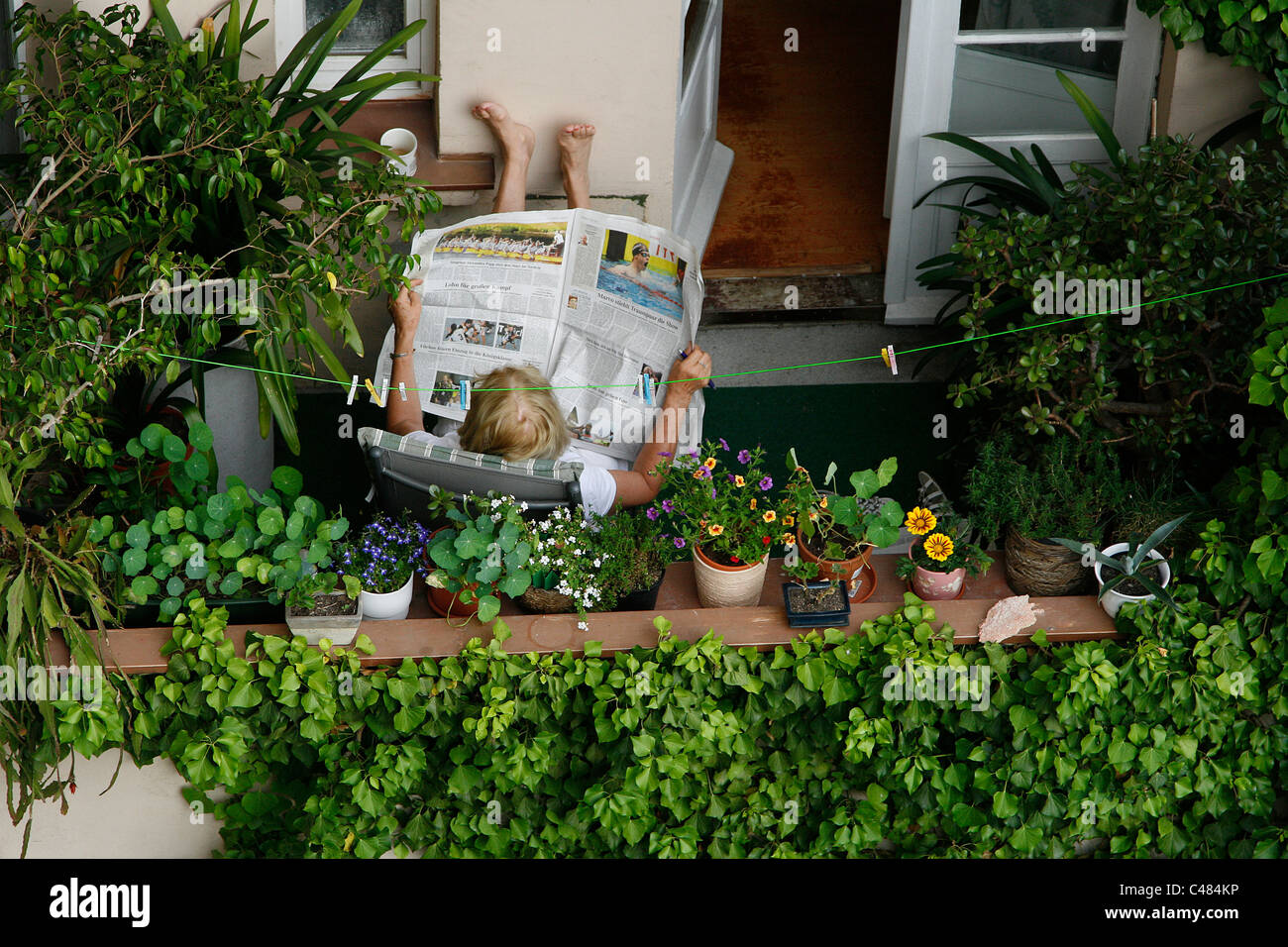 An elderly German woman sitting relaxed at her balcony reading newspaper surrounded by flower pots in Leipzig, Germany - Stock Image