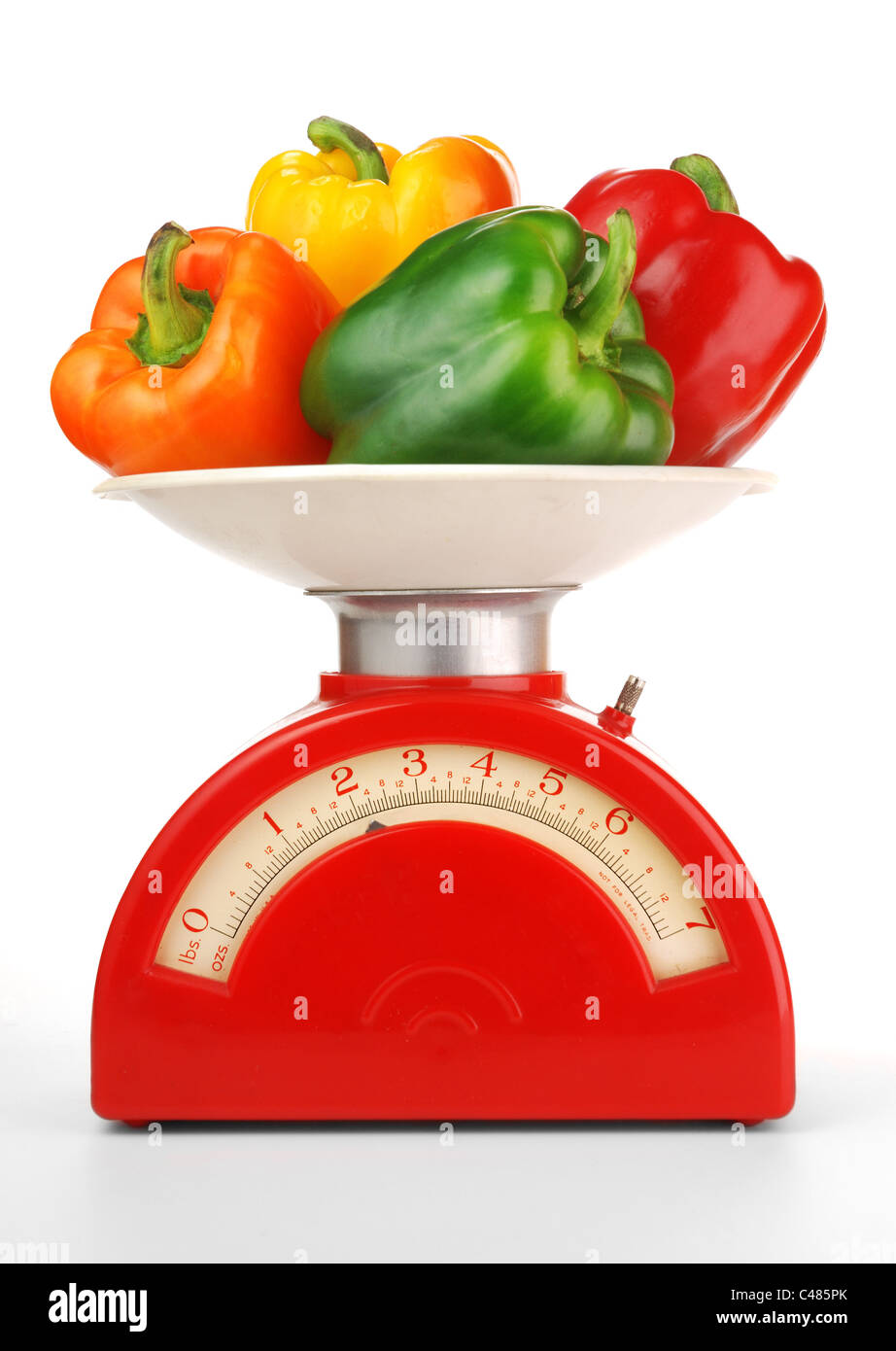red, orange, yellow, green bell peppers on a vintage kitchen scale - Stock Image