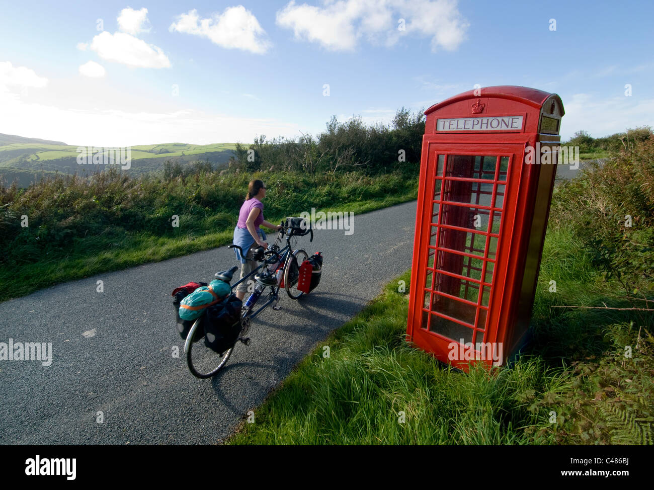 Old Red telephone box on the top of Exmoor, with cyclist and tandem, Devon - Stock Image