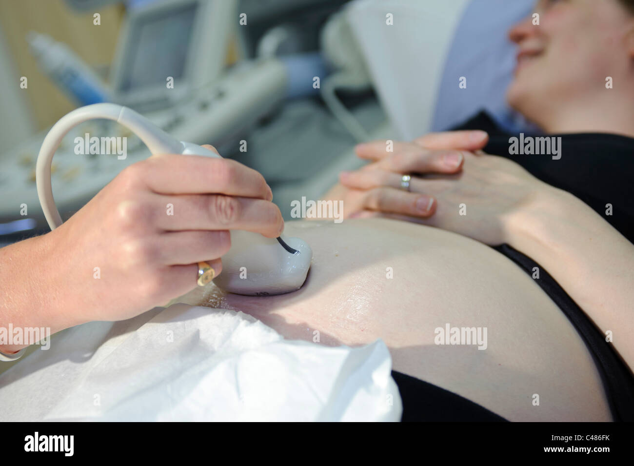 pregnant woman on patient consulting table having ultrasound scan by female doctor - Stock Image