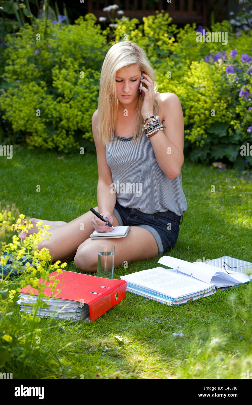 Young girl student chatting and socializing on moblie phone while studying in the garden Stock Photo