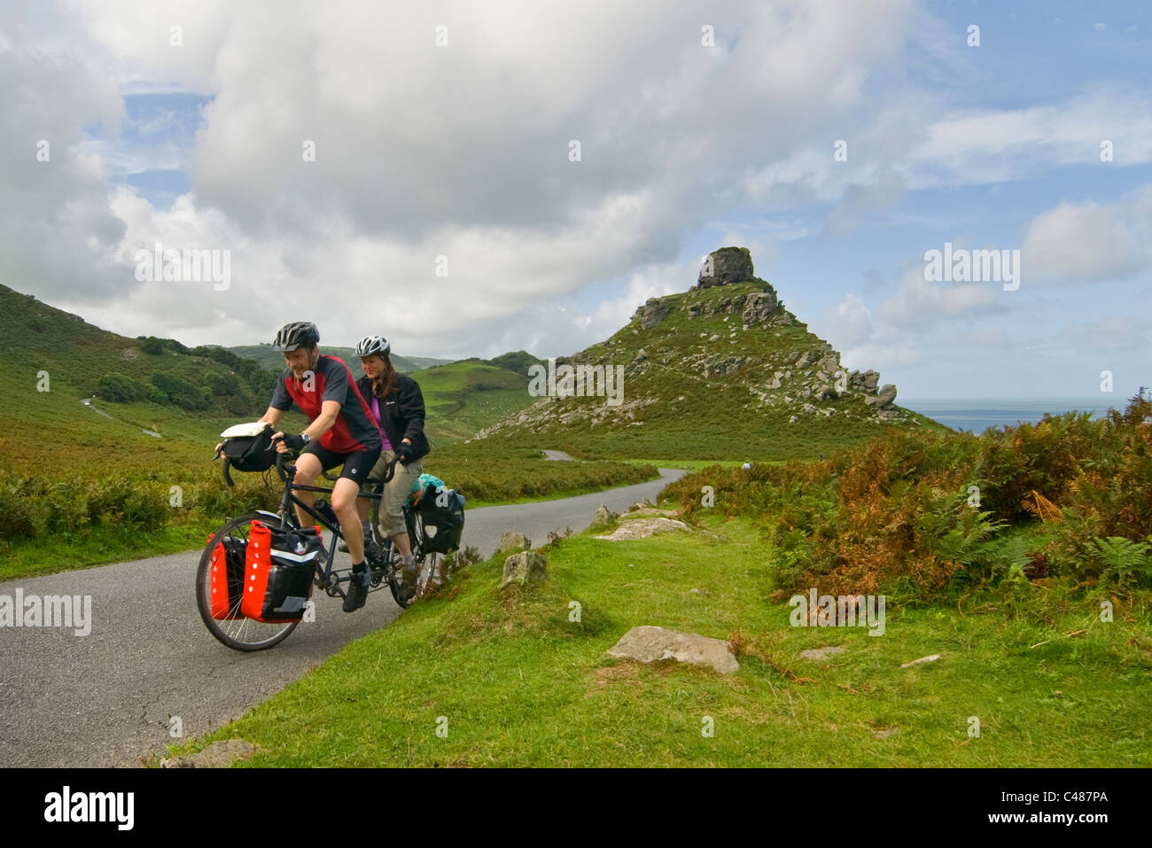Tandem cyclist by Castle Rock, Valley of the Rocks, Lynton, Devon, - Stock Image
