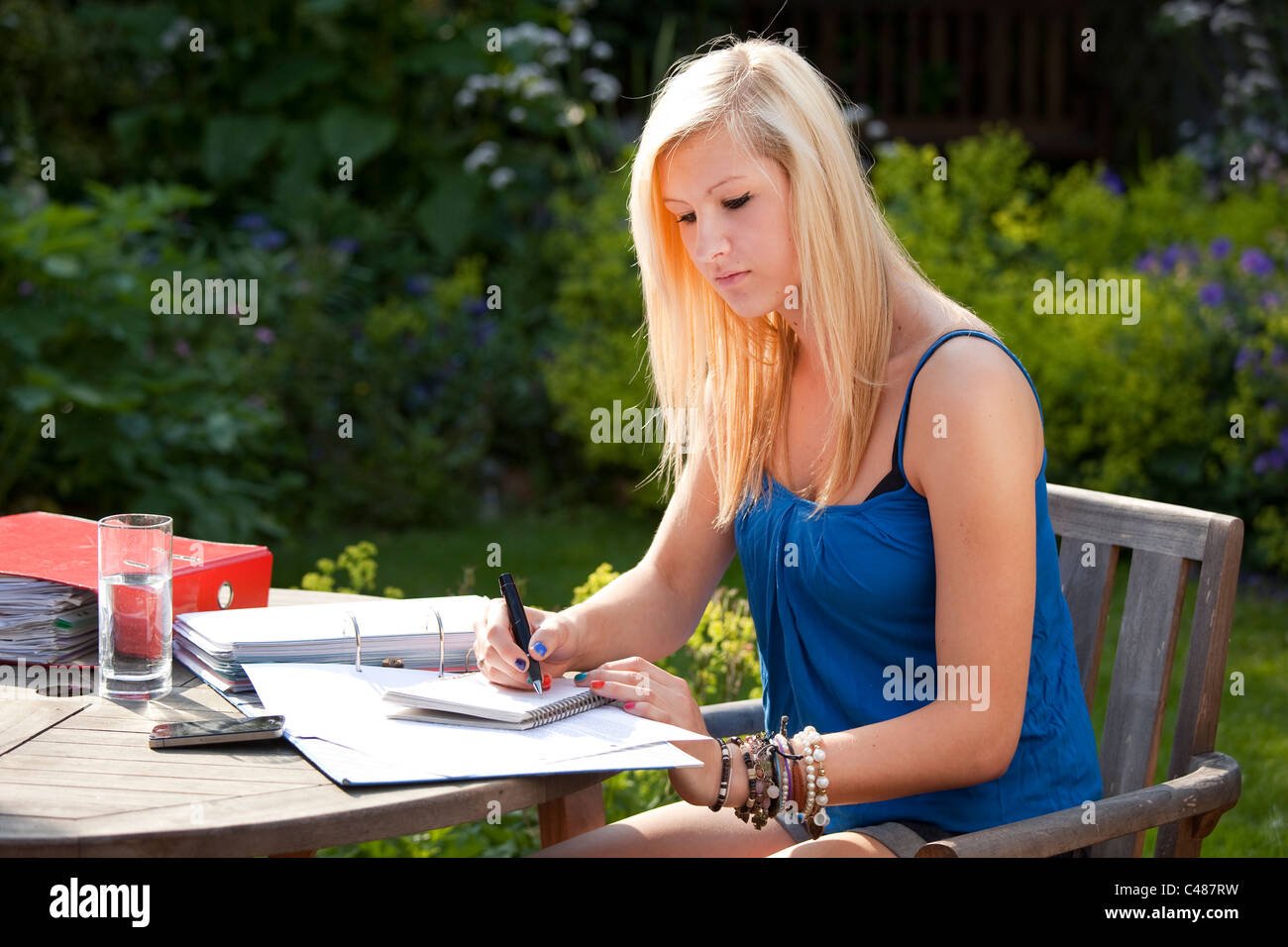 Young girl Student studying outside in the garden with notepad and files for exams - Stock Image