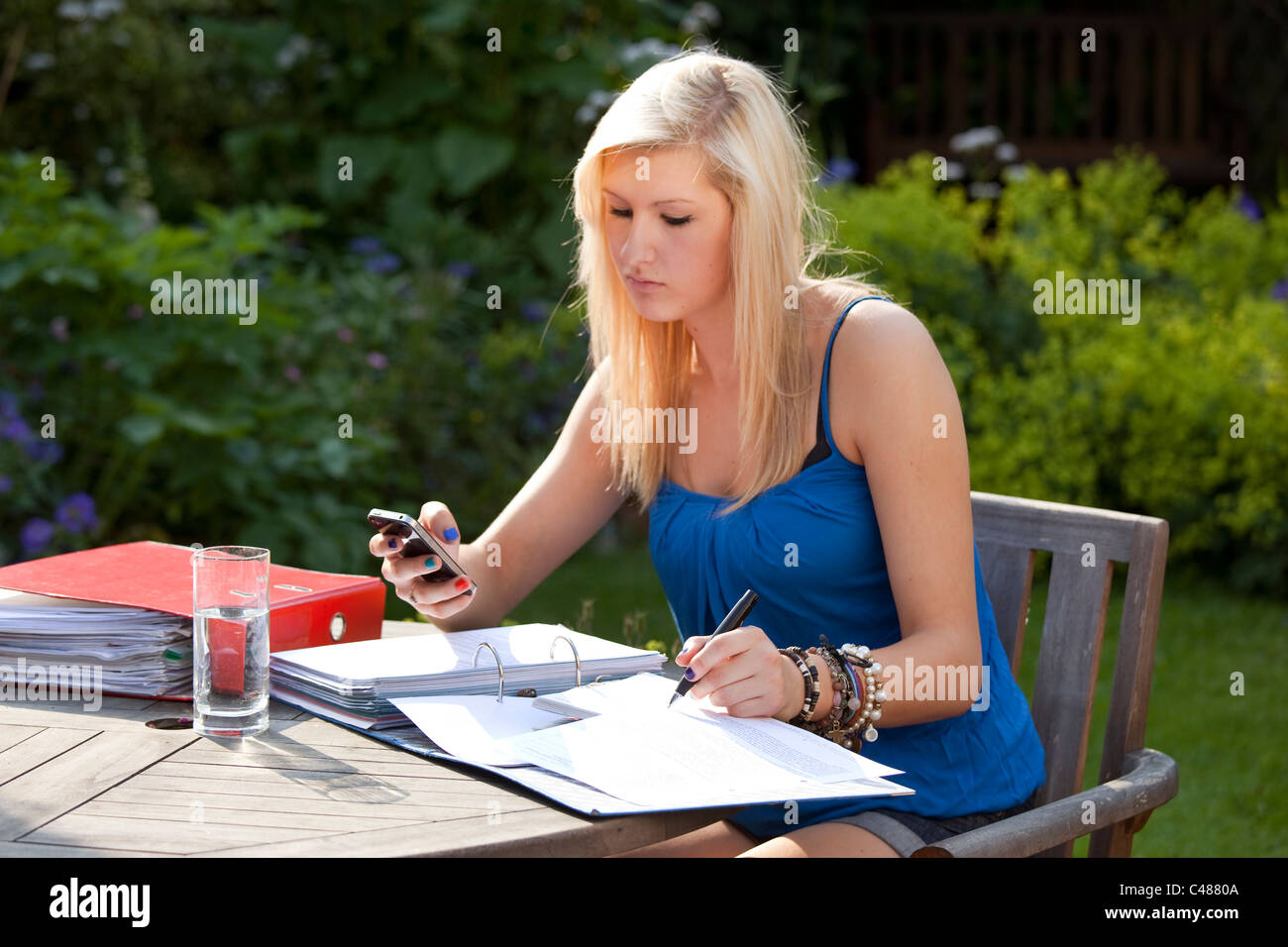 young girl student texting on moblie phone while studying in the garden for exams Stock Photo
