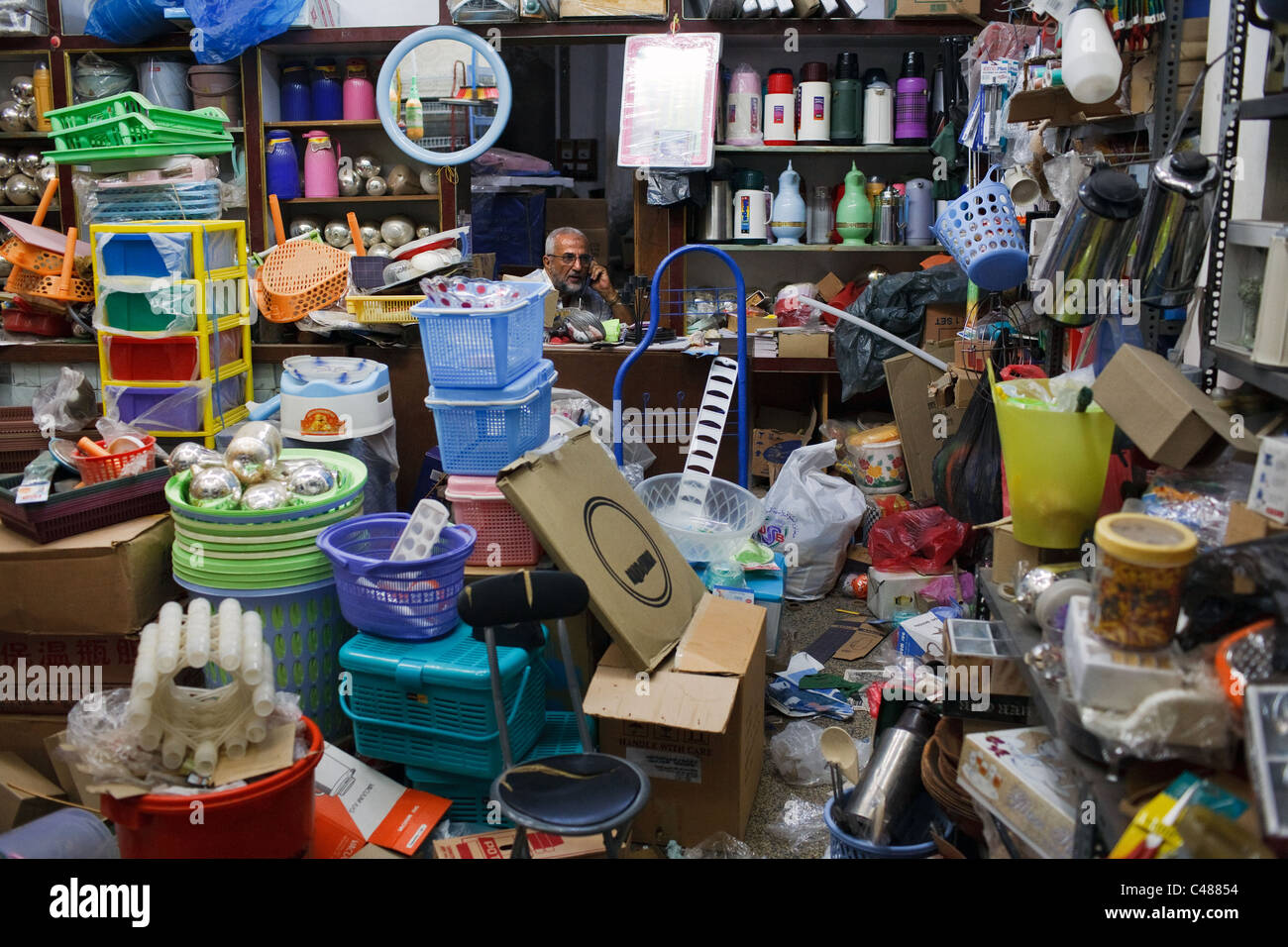 A shopkeeper inside his shop with household goods in Aden, Yemen. - Stock Image