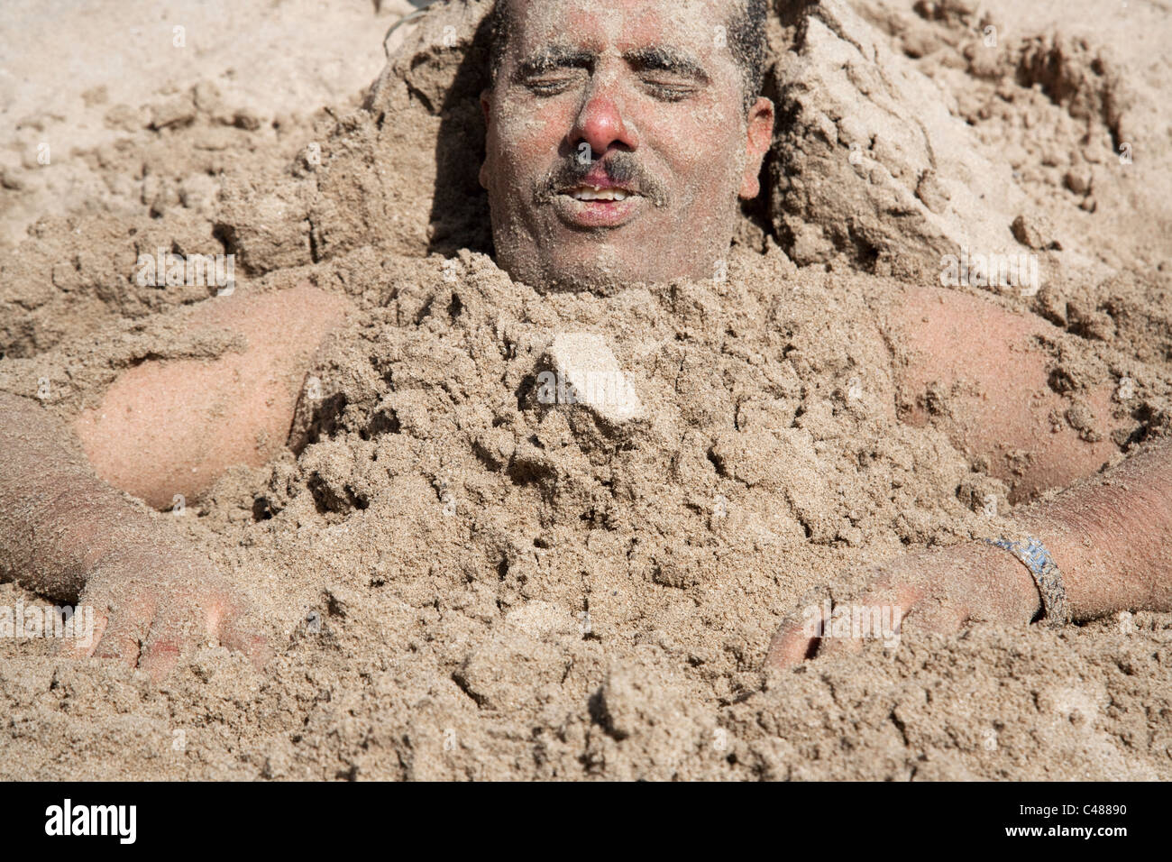 A man buried in the sand on the beach on the coast of Red Sea in Aden, Yemen. - Stock Image