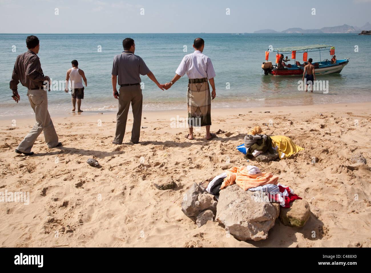 Yemeni men holding hands on the beach on the coast of Red Sea in Aden, Yemen. - Stock Image