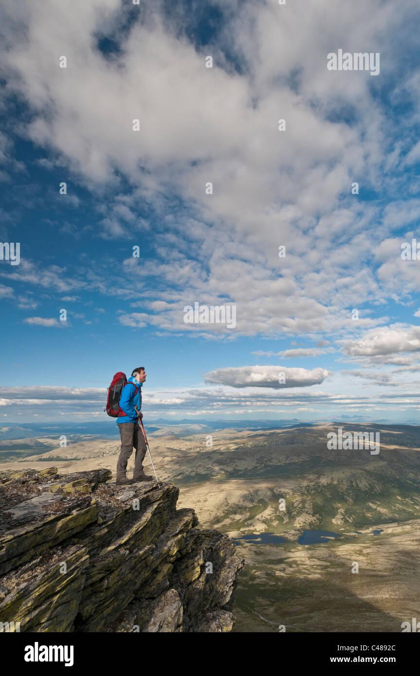 Wanderer auf einem Gipfel im Alvdal Vestfjell, in der Ferne der Berg Rendalssoelen, Rendalen, Hedmark, Norwegen - Stock Image