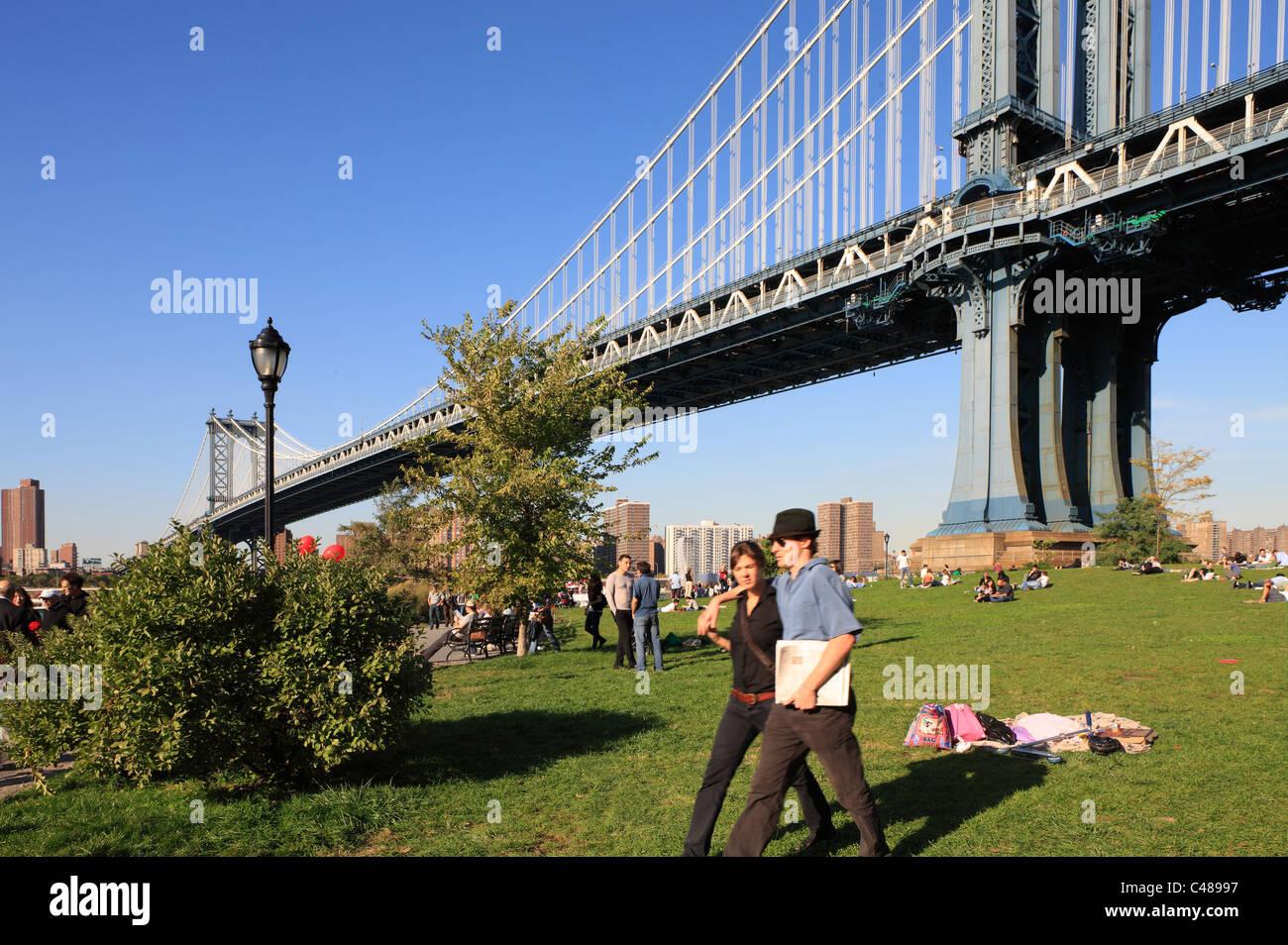 People on the grass under the Manhattan Bridge, New York City, USA - Stock Photo