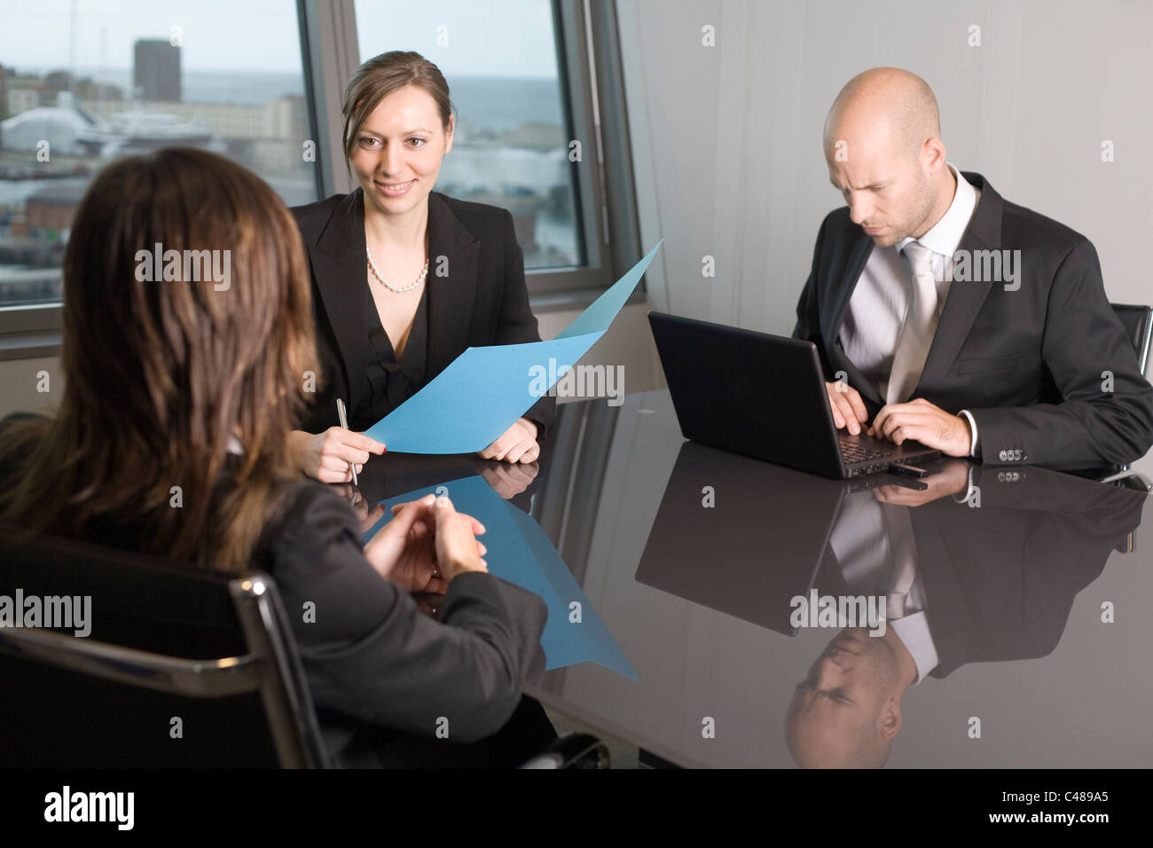 Three persons during a interview in a skyline office - Stock Image