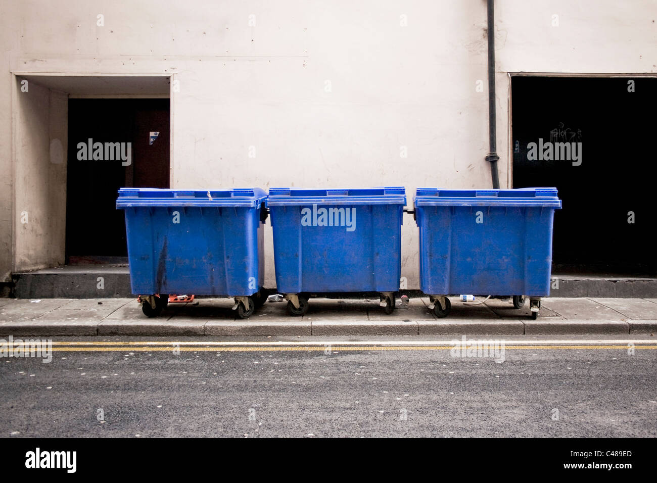 Three large rubbish bins stand at the side of an empty Manchester street. - Stock Image