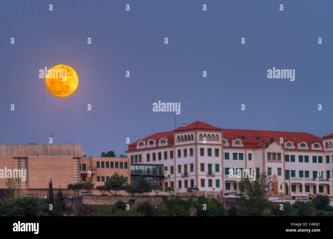 full moon rises over old houses of at cemetario Maior, Portugal - Stock Image